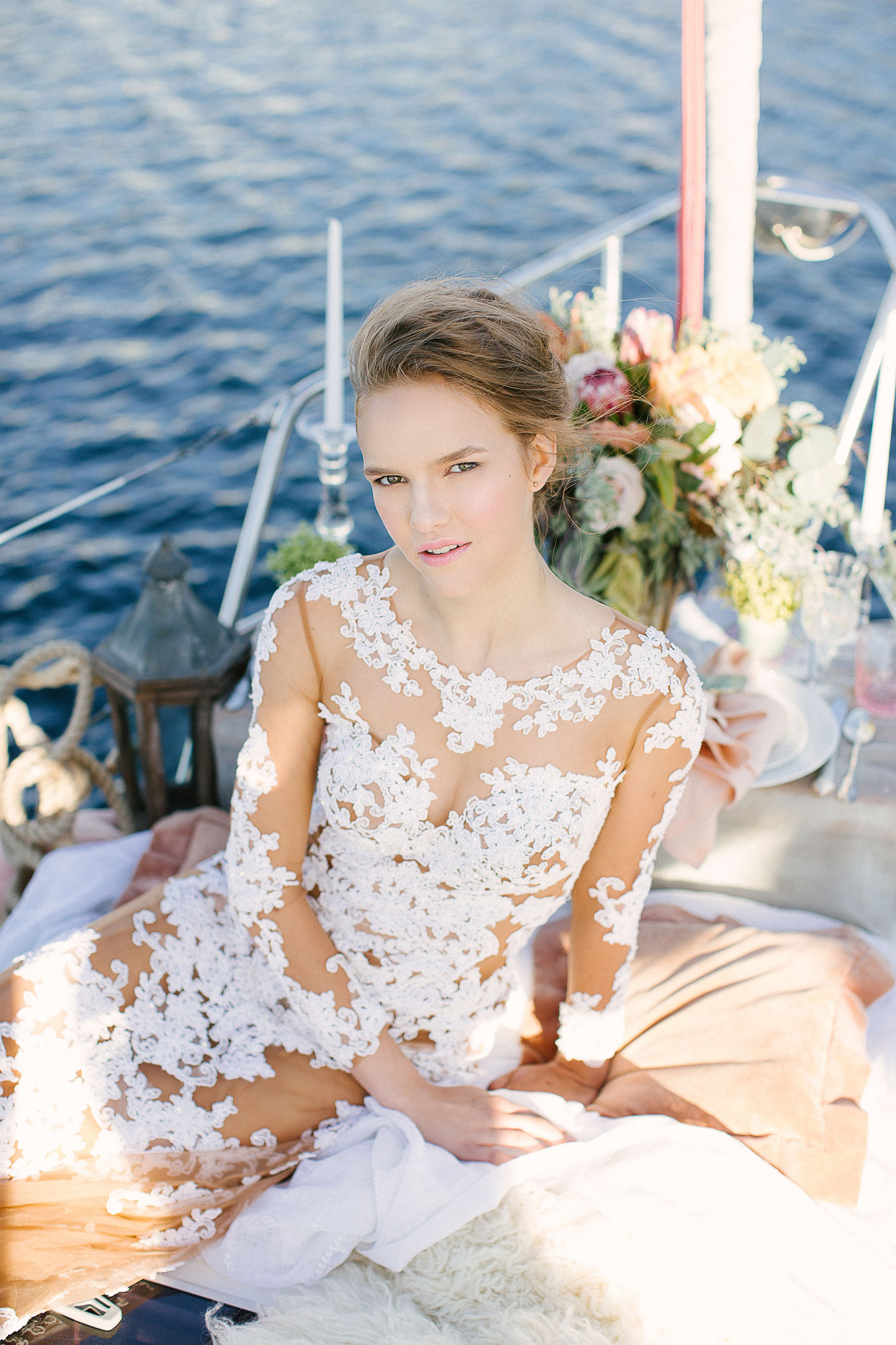 Bride on sailboat in illusion long sleeve sheer wedding dress
