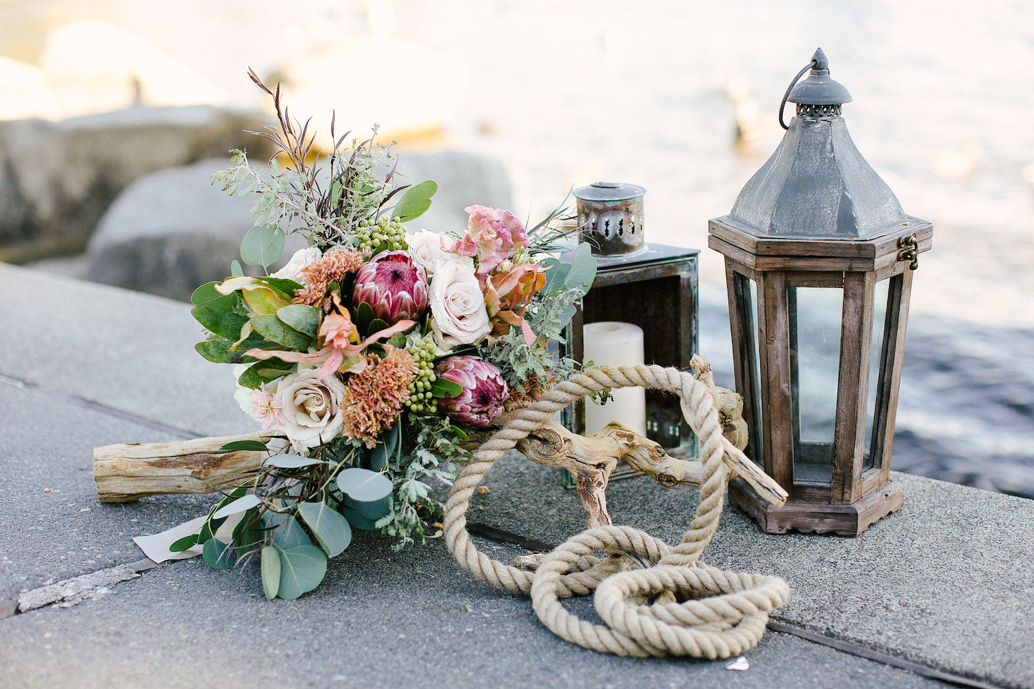 Protea wedding bouquet with driftwood and rustic lanterns