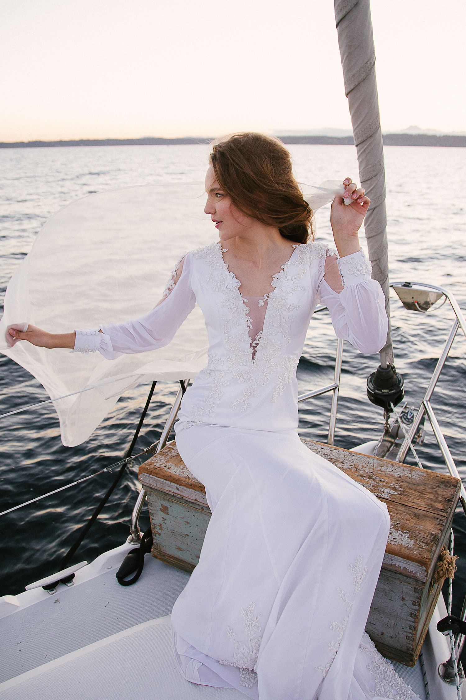 Bride on sailboat in long sleeve vintage inspired wedding dress