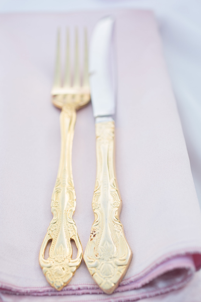 Gold flatware on light pink napkin
