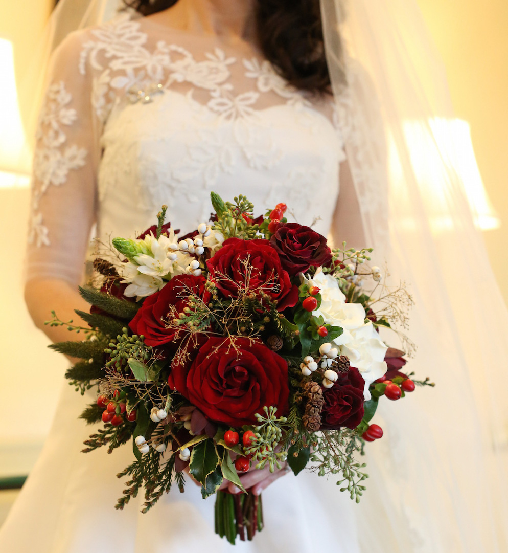 Festive dcor for weddings with a holiday or christmas theme red rose winter wedding bouquet junglespirit Image collections