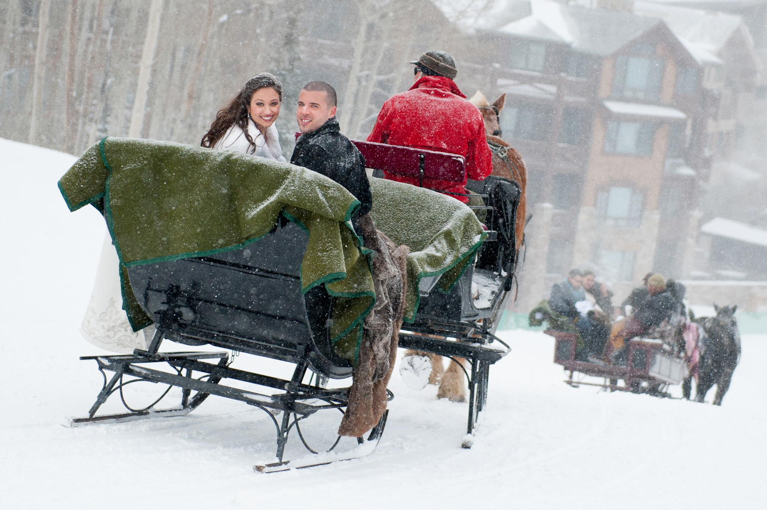 Bride and groom in snow sleigh after ceremony