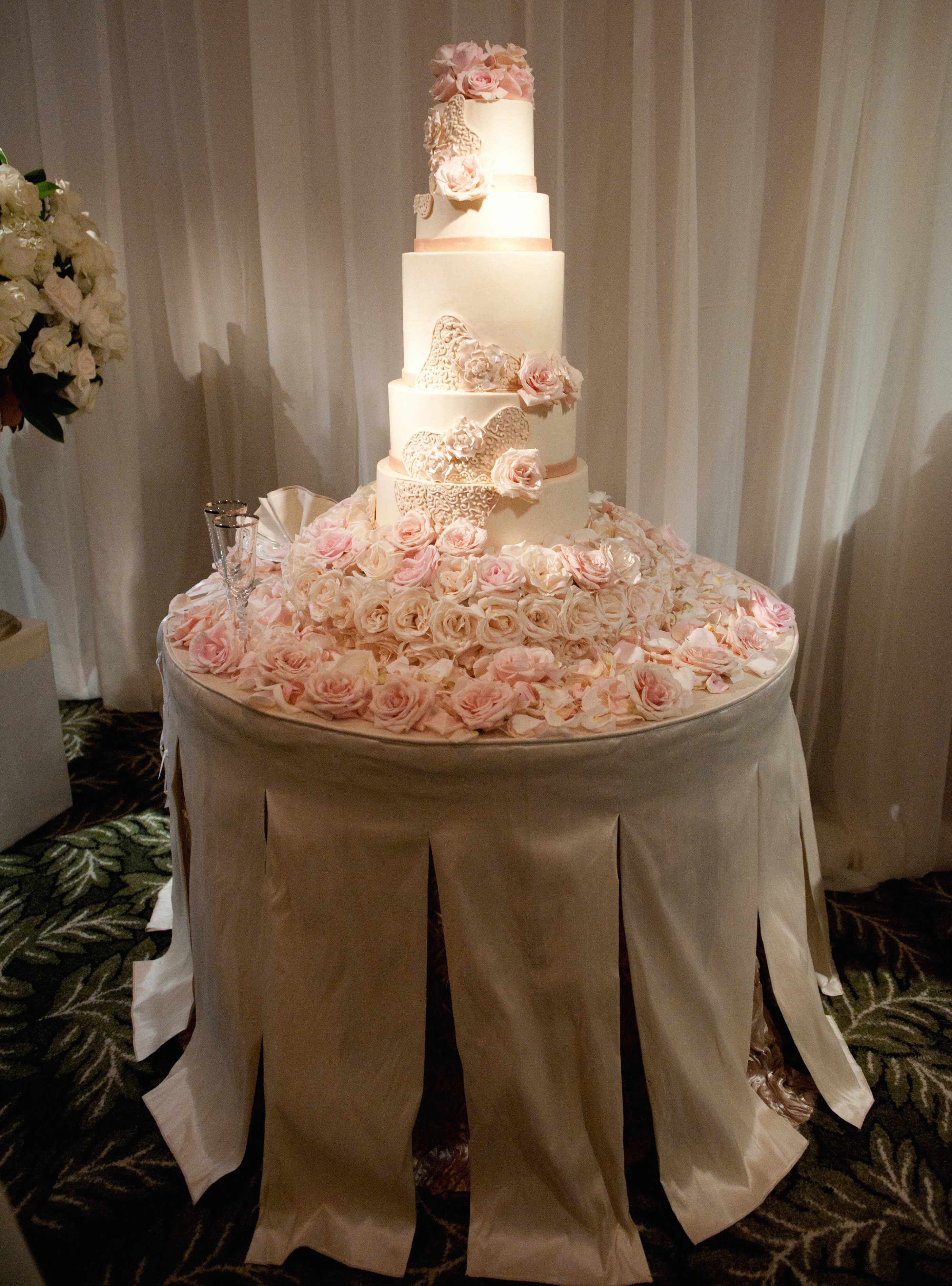 Cake stand on table with blush and ivory roses