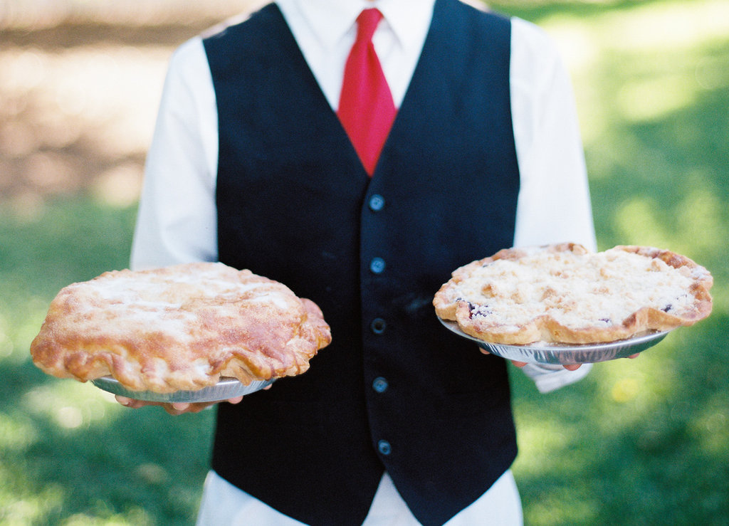 Server at wedding holding two pies