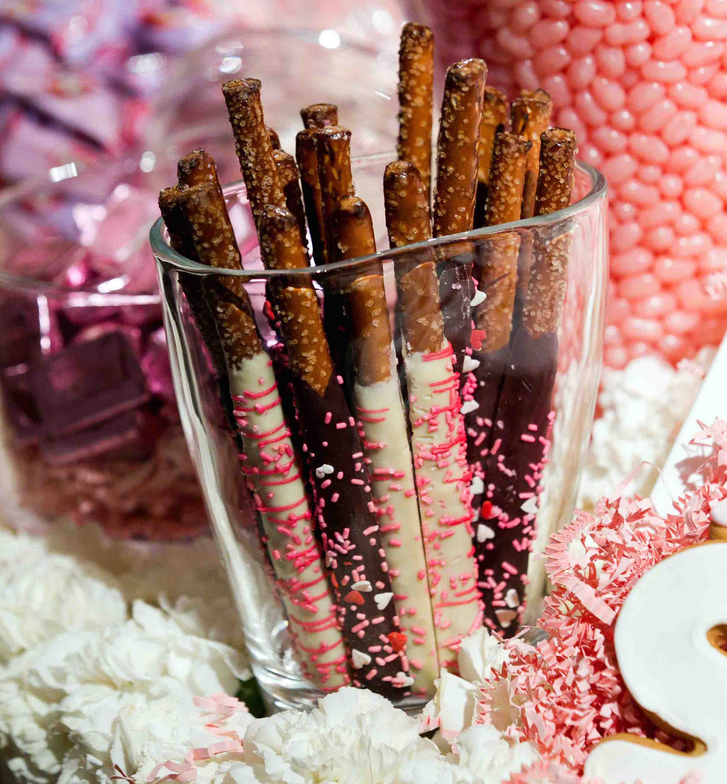 Pretzel sticks covered with white and dark chocolate with sprinkles