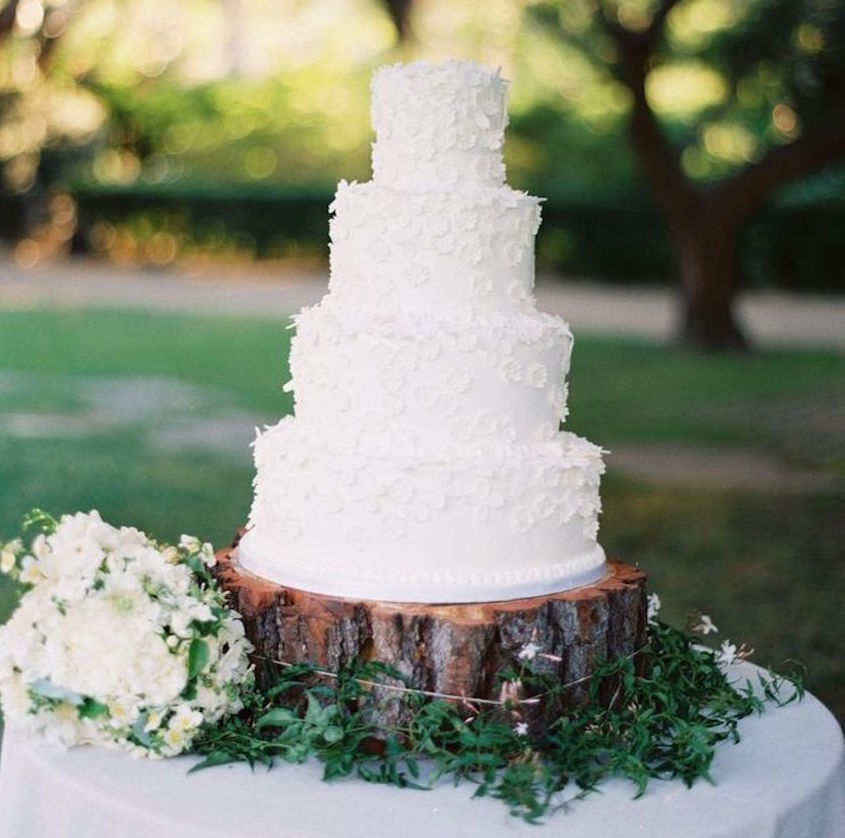 White Wedding Cake On Tree Trunk Slab At Outdoor