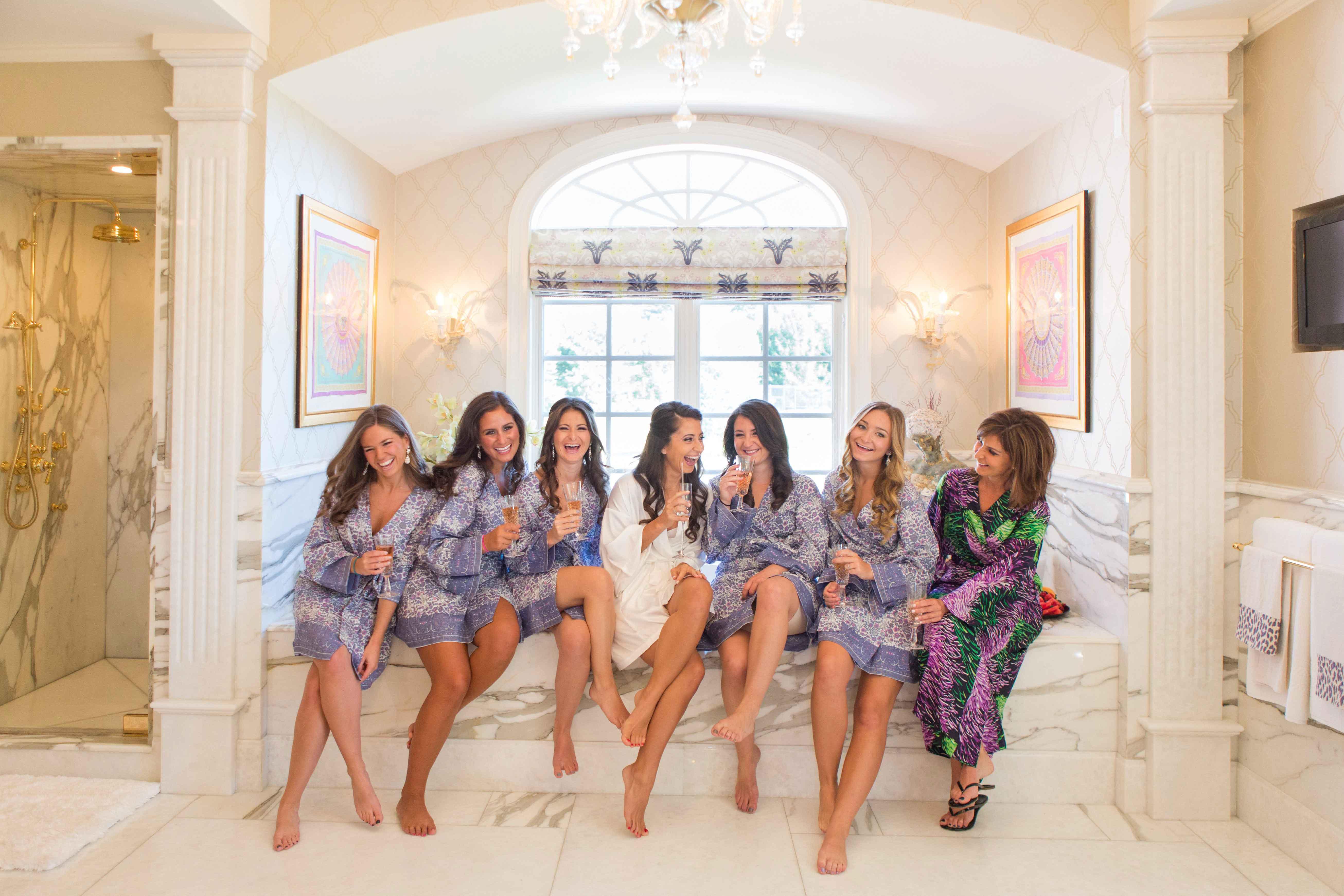 Bridesmaids in marble bathroom in floral print robes