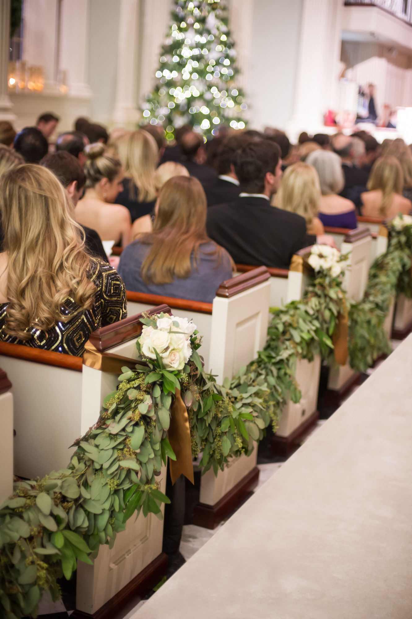 Green garlands with white roses on church pews