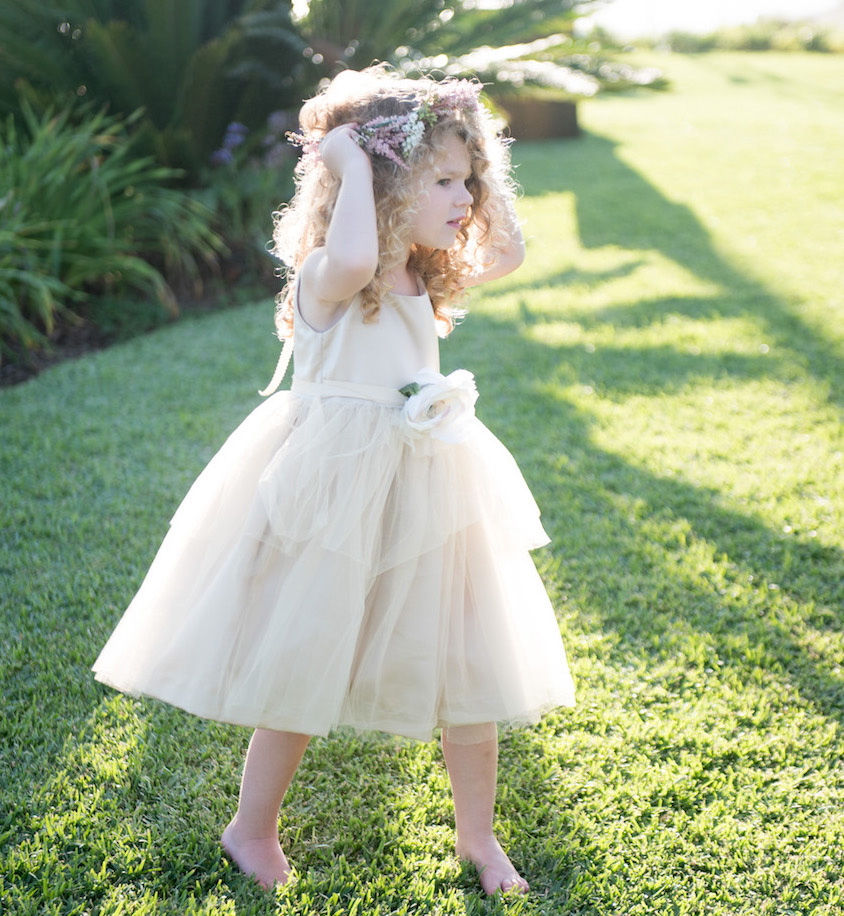 Flower girl with curly hair in tan dress