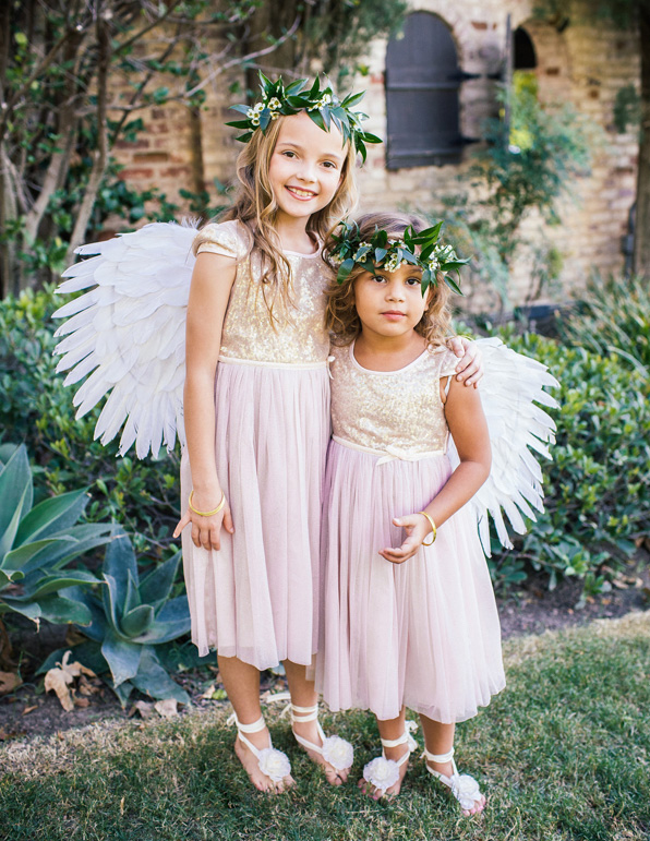 Flower girls in gold sequin and pink dresses with fairy wings