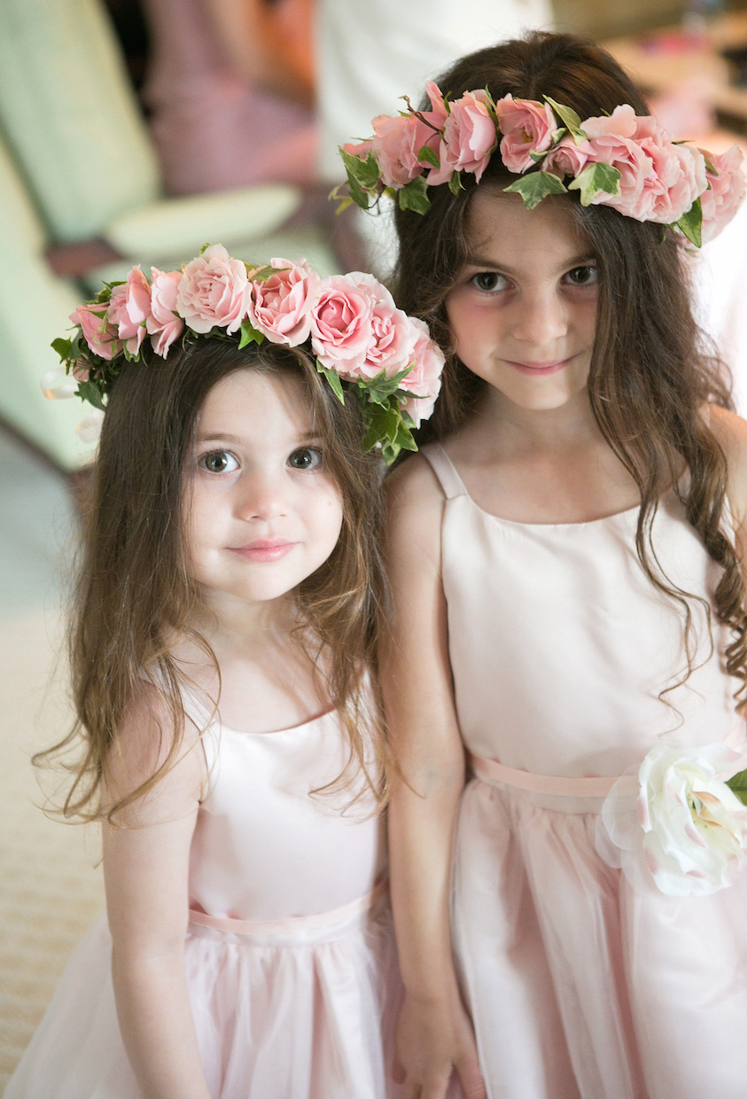 Flower girls in light pink dresses and pink rose flower crowns
