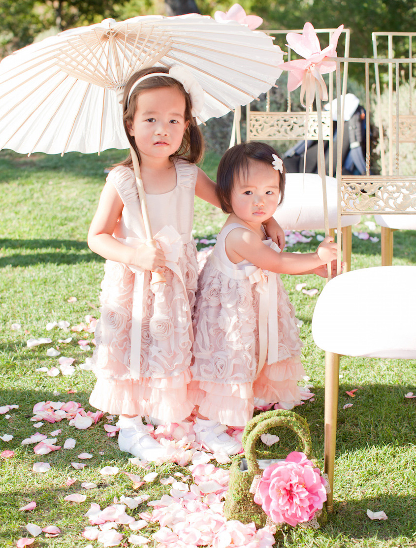 Asian American flower girls in light pink dresses and parasols