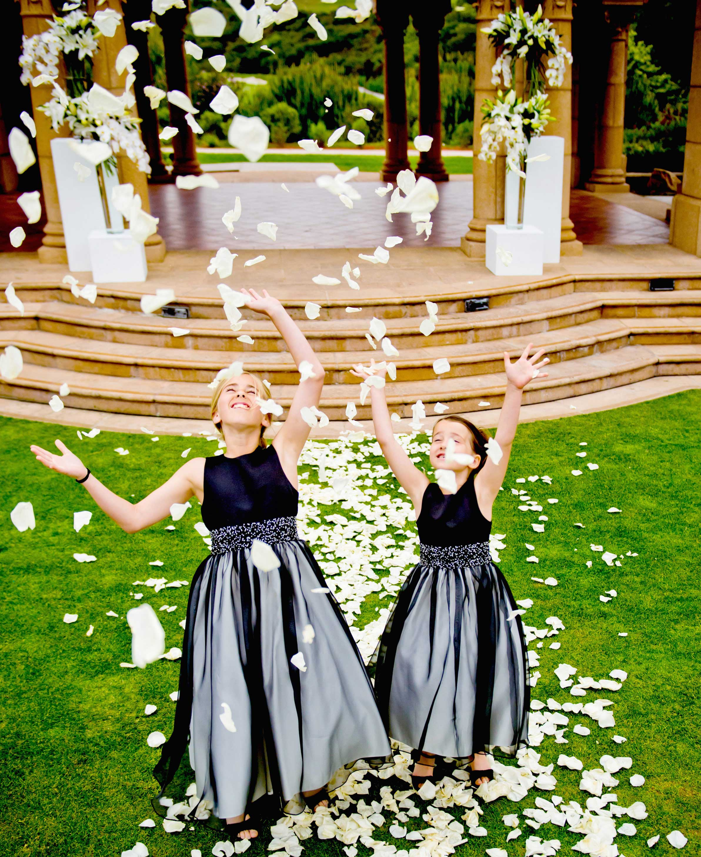 Flower girls tossing rose petals in black dresses
