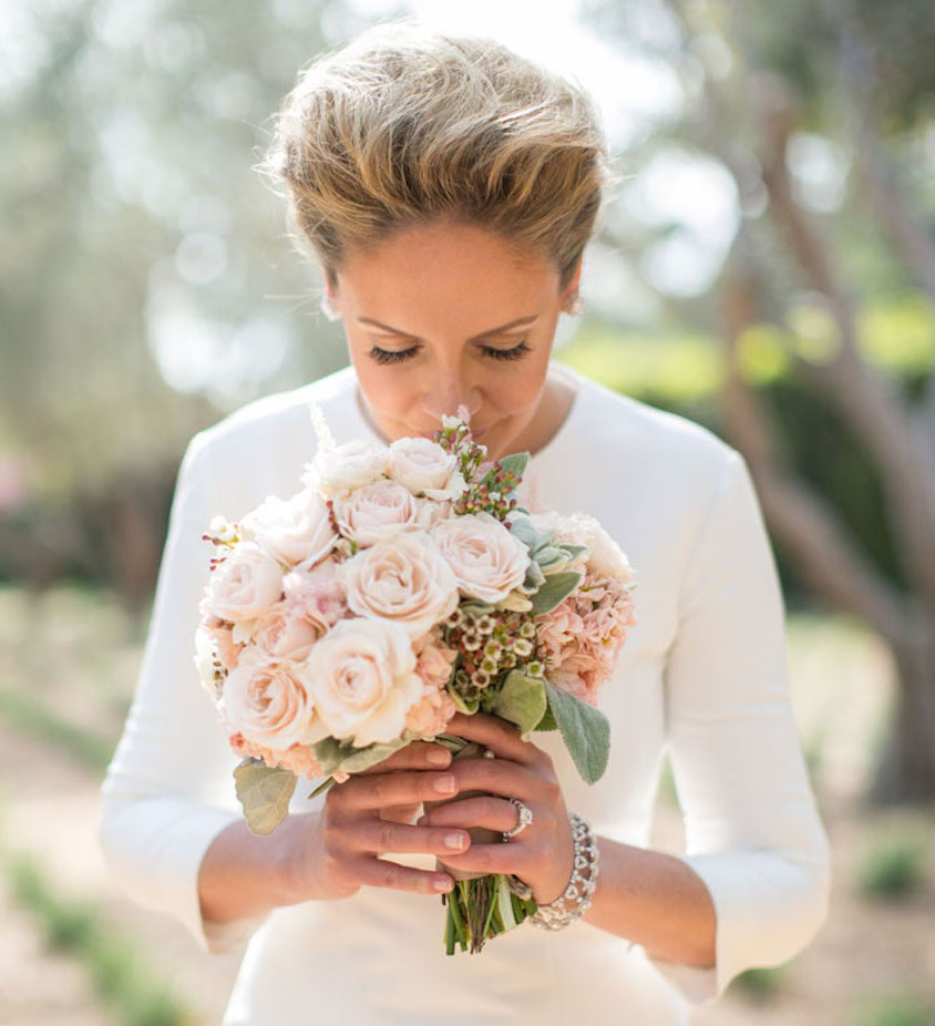 Bride smelling light pink bouquet