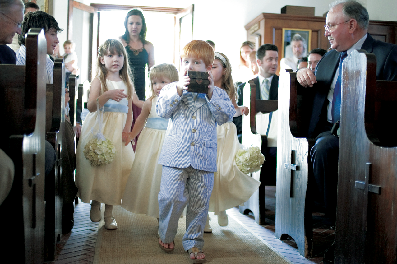 ring bearer in sear-sucker suit and flip flops with treasure chest