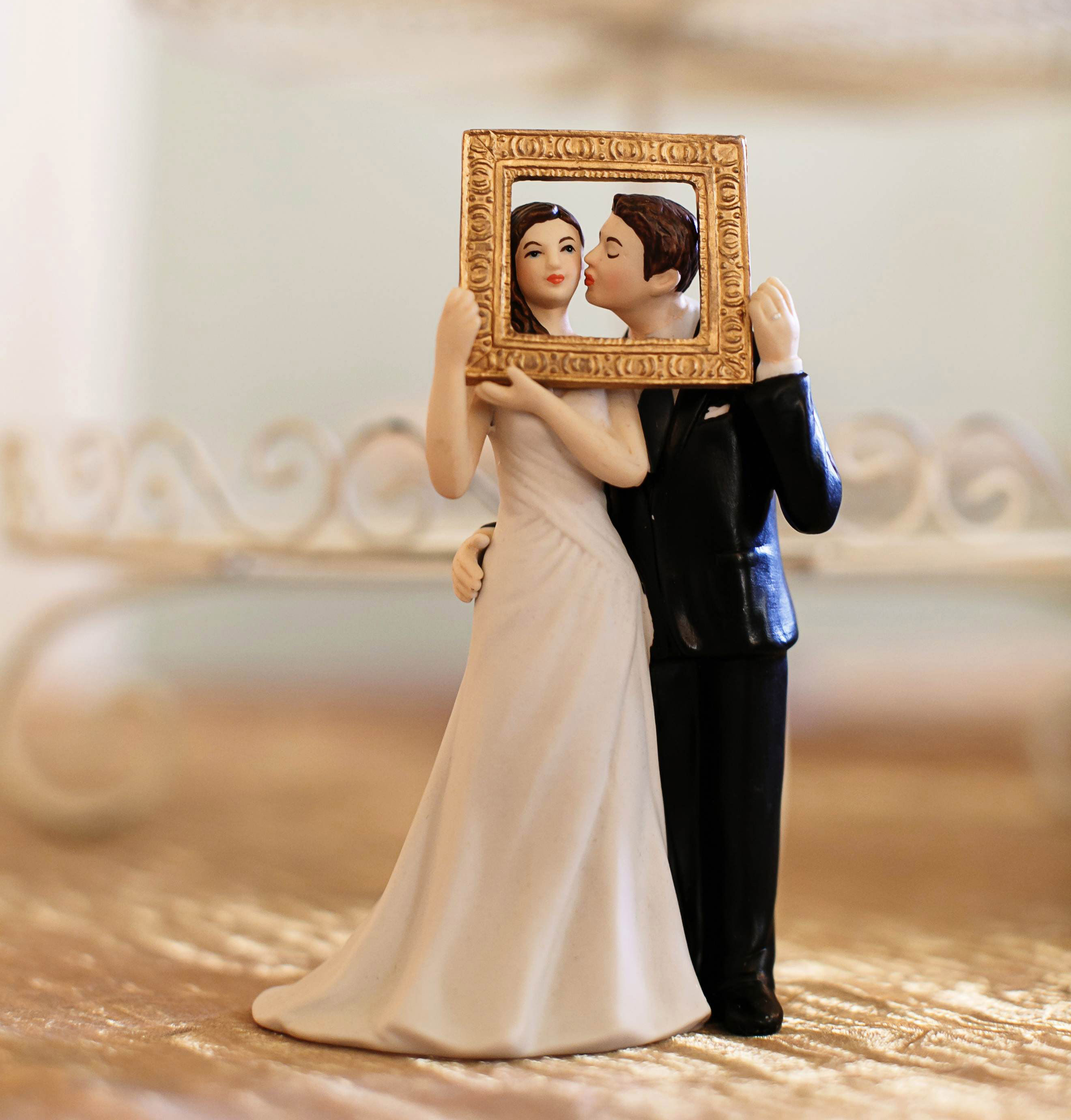 cake topper with bride and groom holding an ornate gold frame