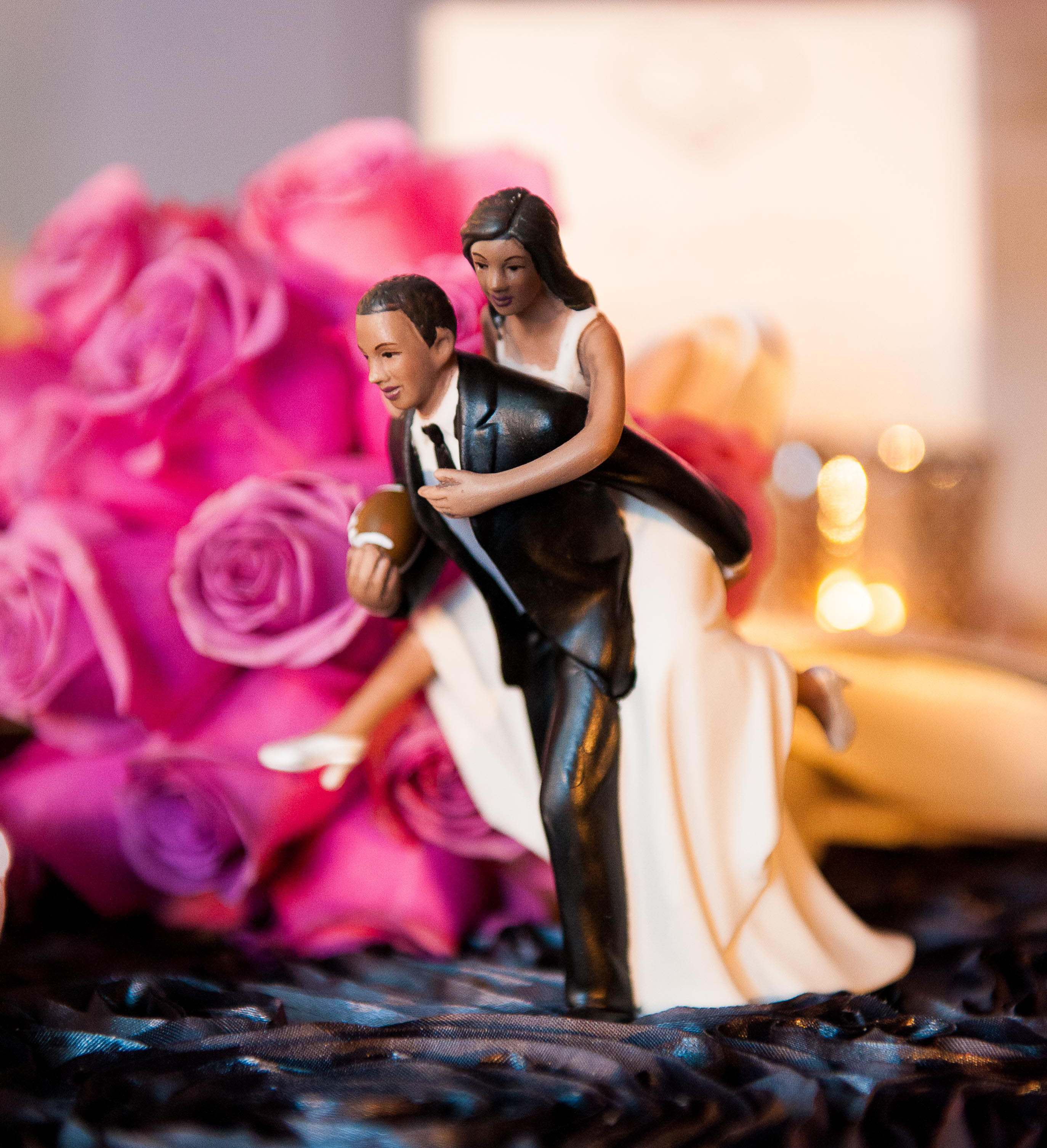 football player wedding cake topper with bride piggyback riding