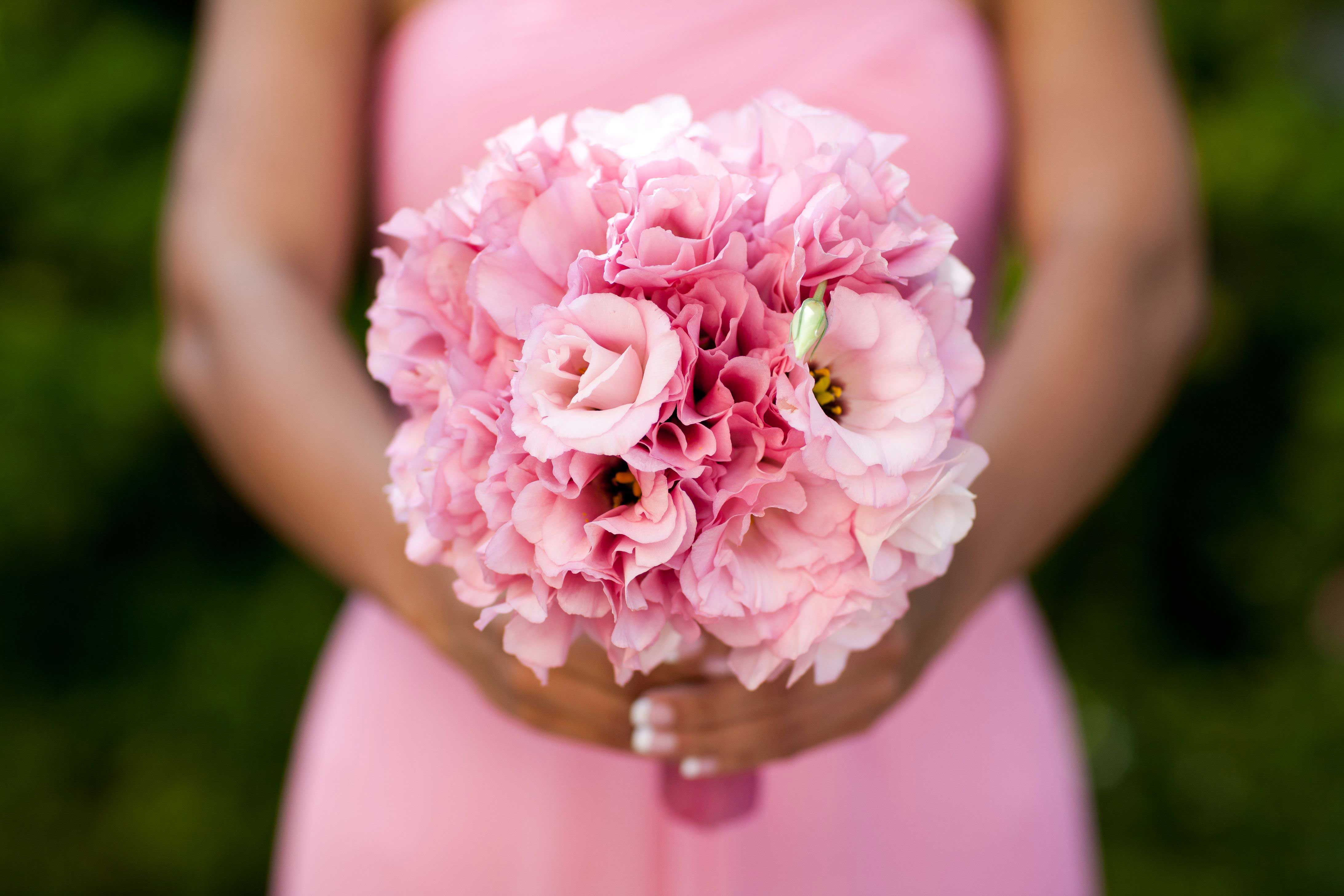Bridesmaid in pink dress holding pink bouquet