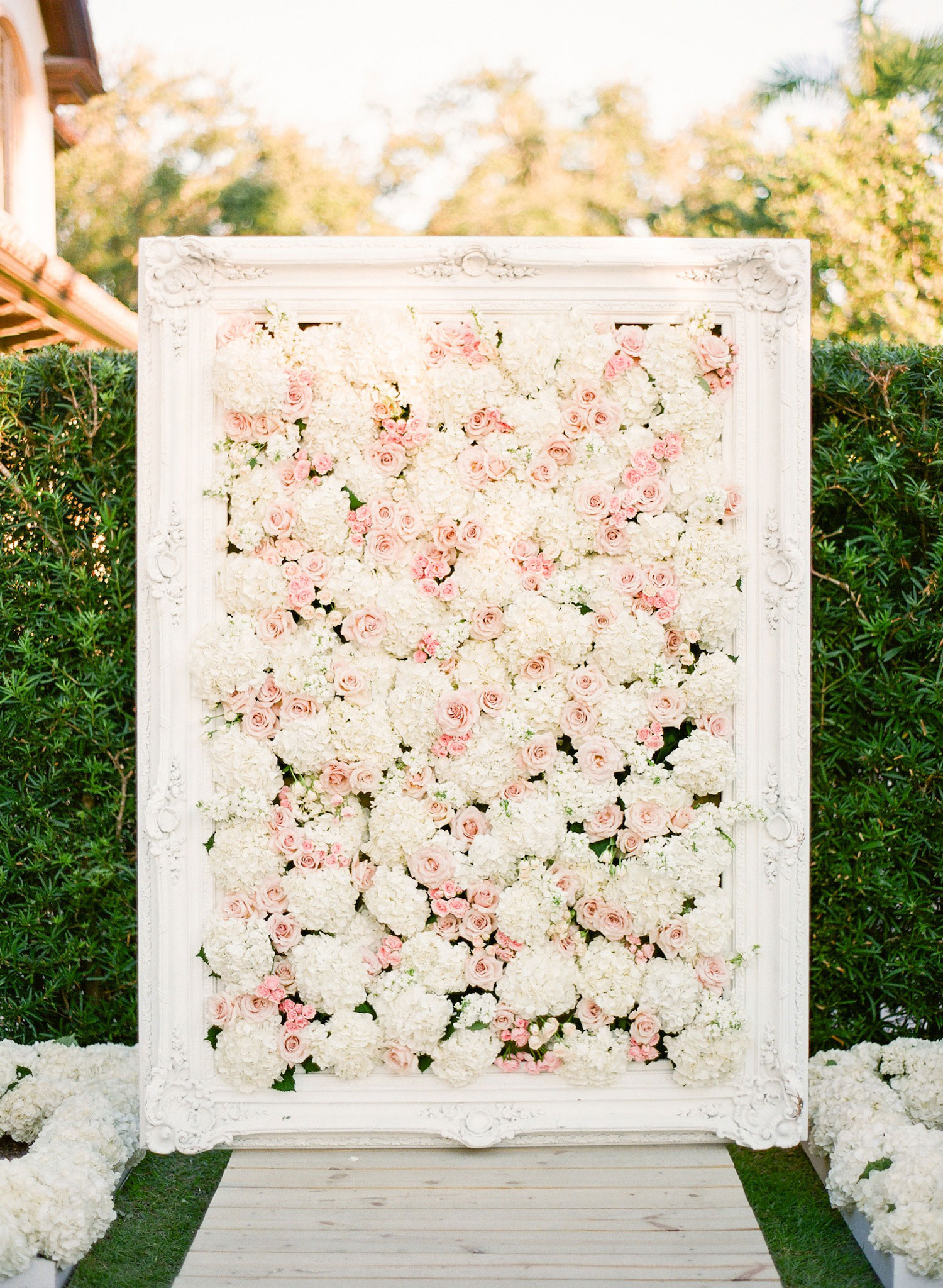 Pink and white flower wall at outdoor ceremony
