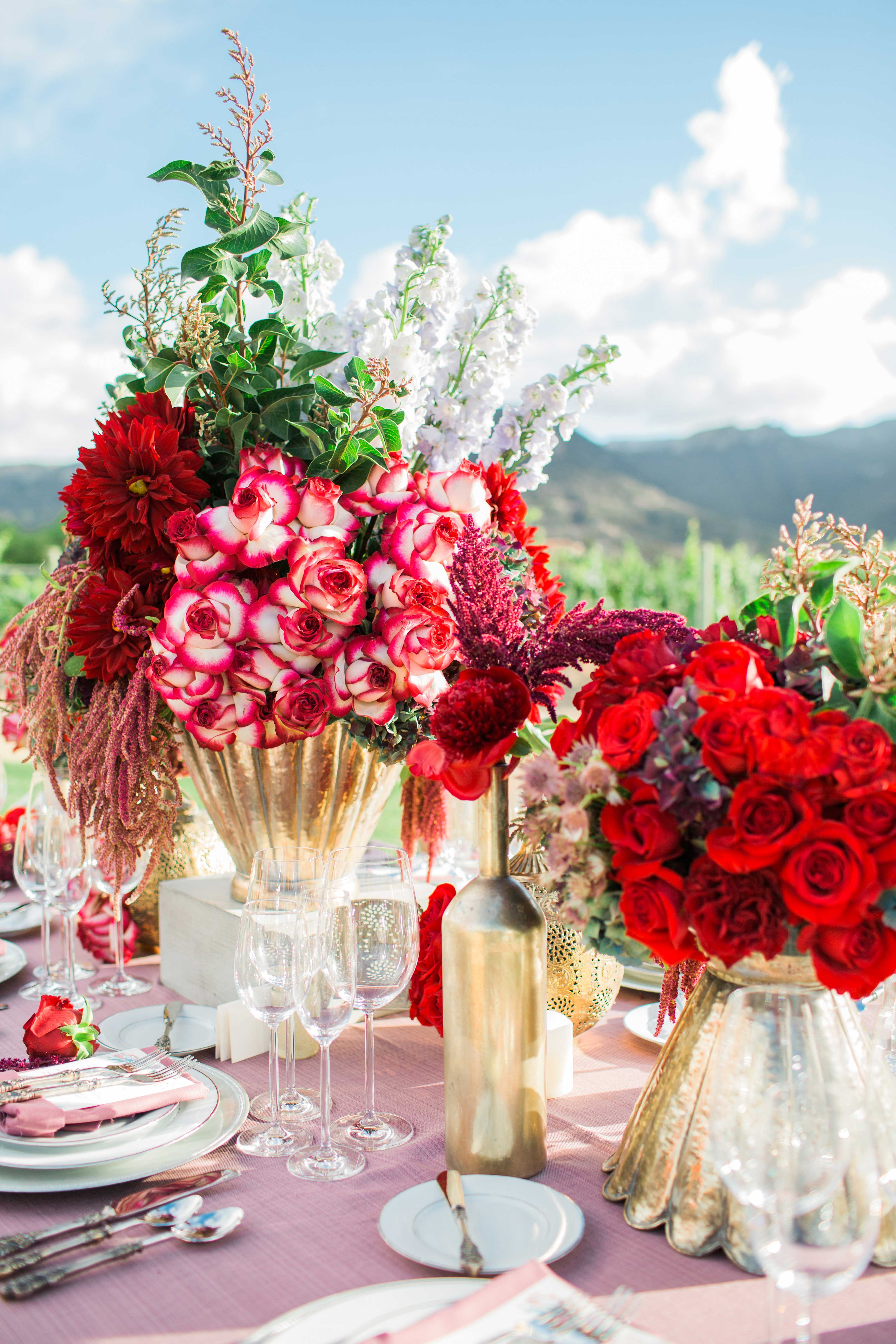 Red reception centerpieces at outdoor wedding