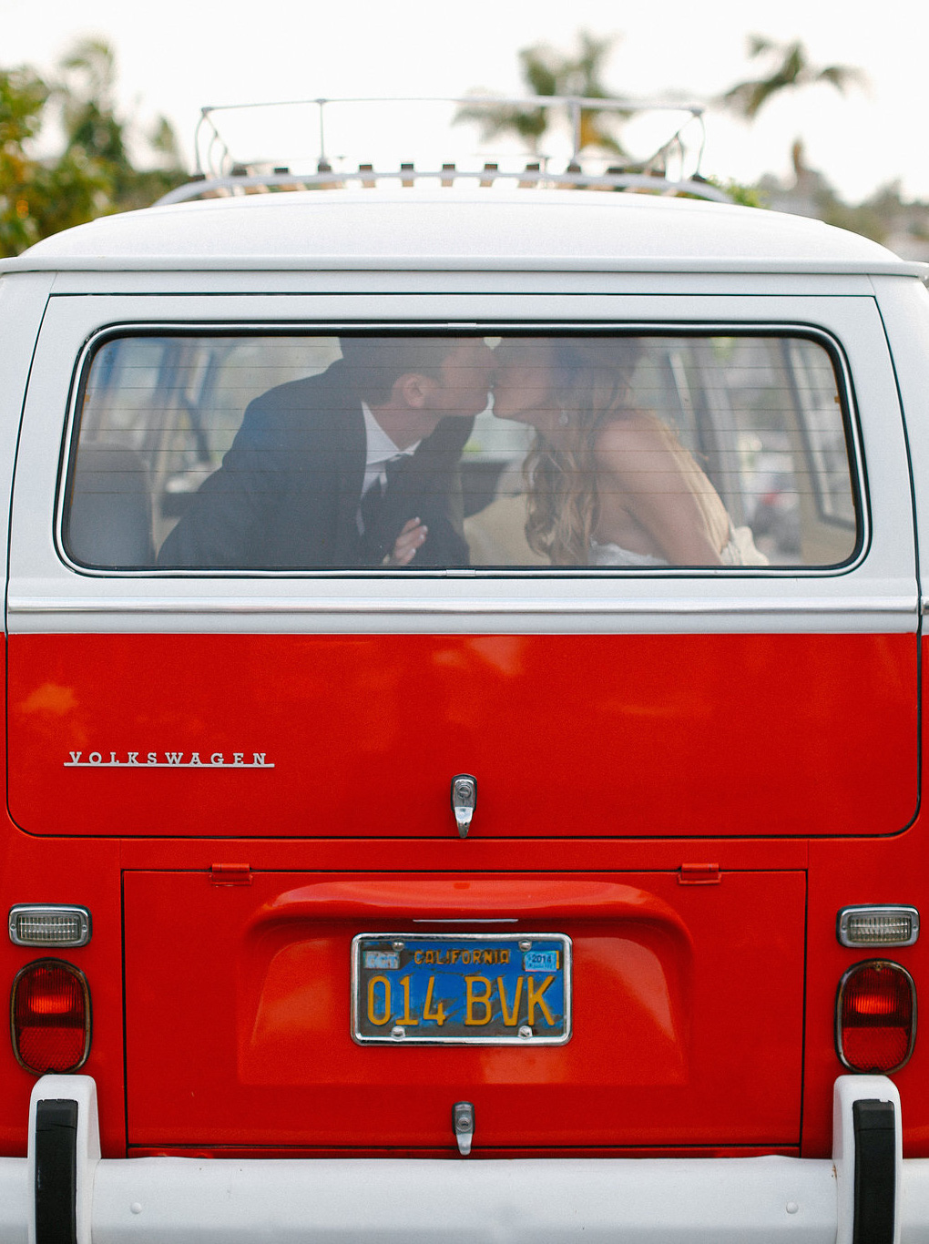Bride and groom kiss in back of red VW bus