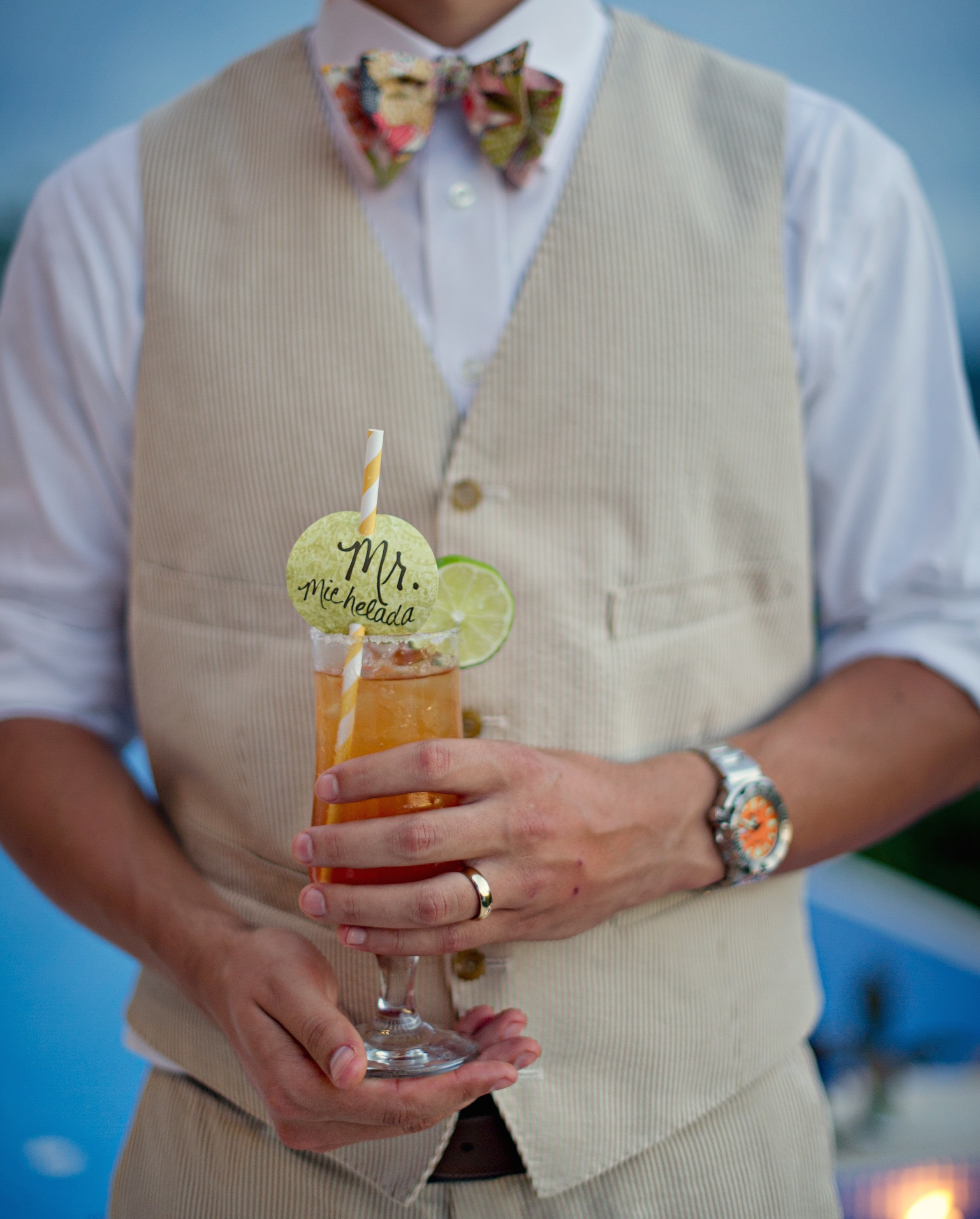 Groom holding striped straw cocktail at wedding