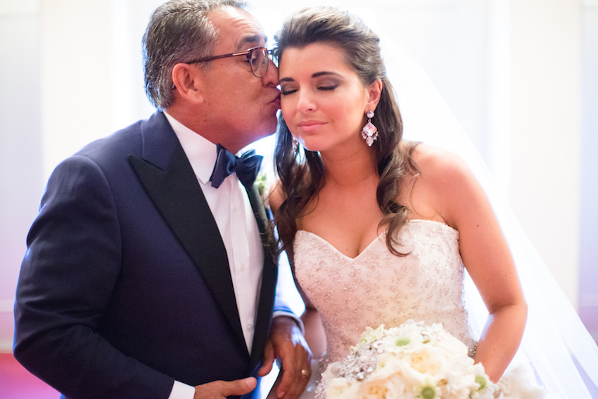 Father of bride kissing bride on wedding day