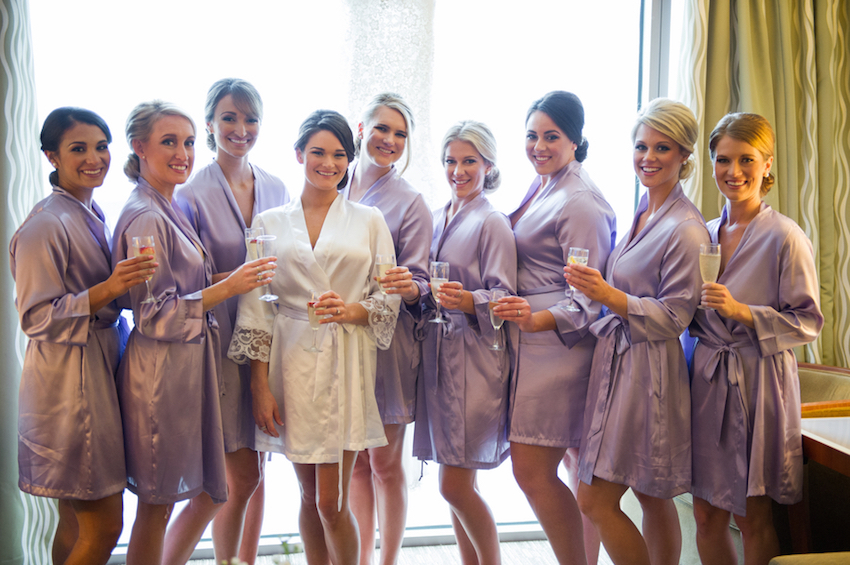 bride in white lace robe, bridesmaids in lavender robes