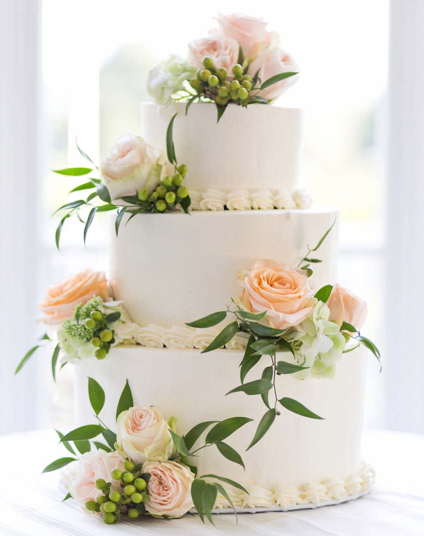 White wedding cake with white and peach roses