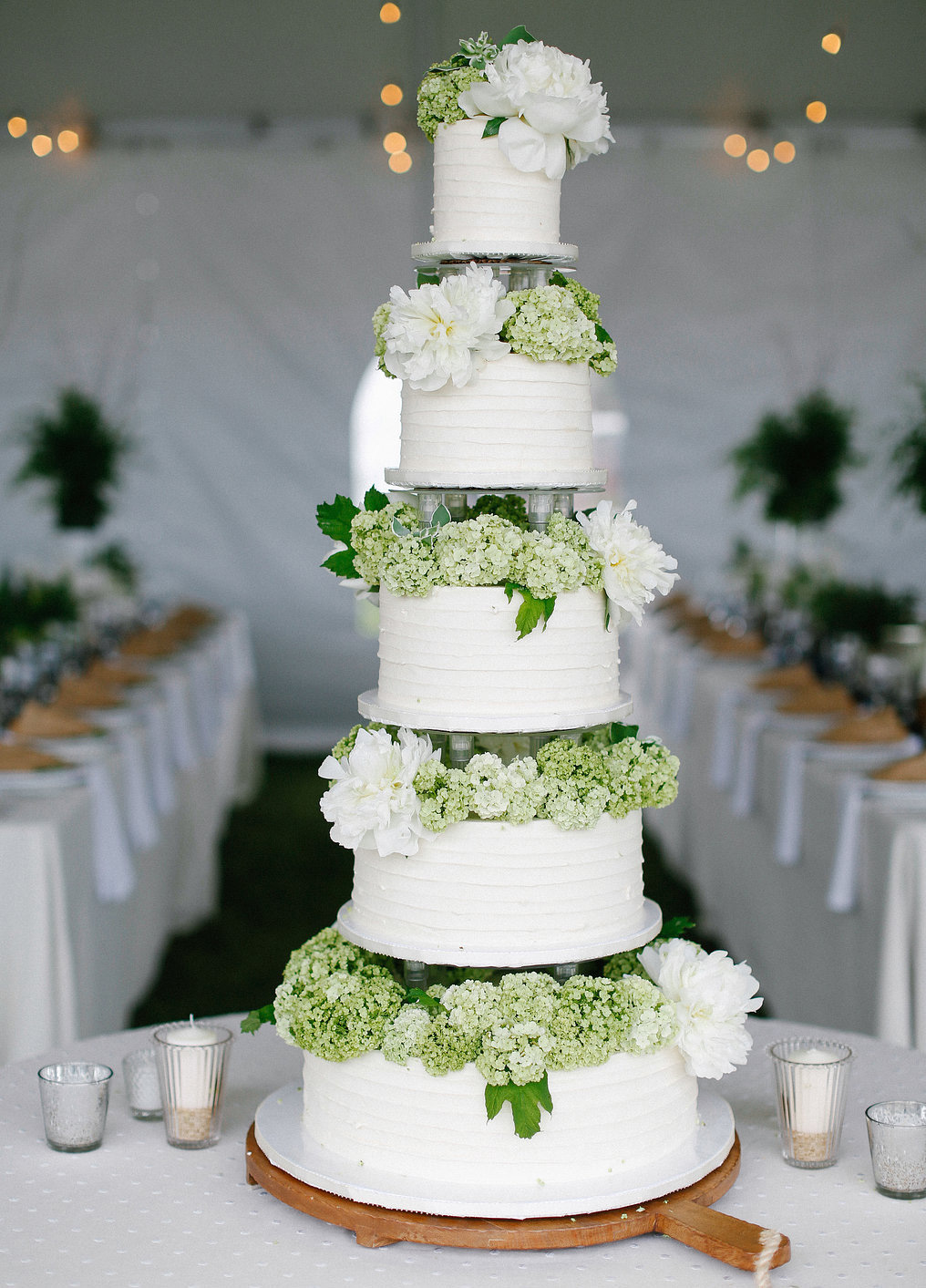 Tall wedding cake with white and green hydrangea tiers