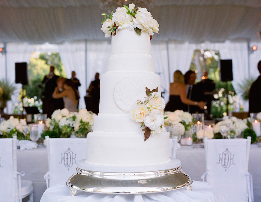 White wedding cake with monogram and fresh flowers