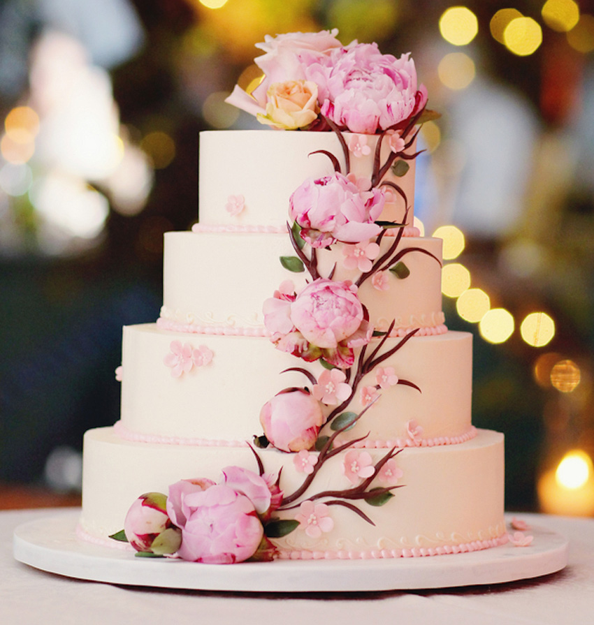 White wedding cake with pink flowers to resemble cherry blossom tree