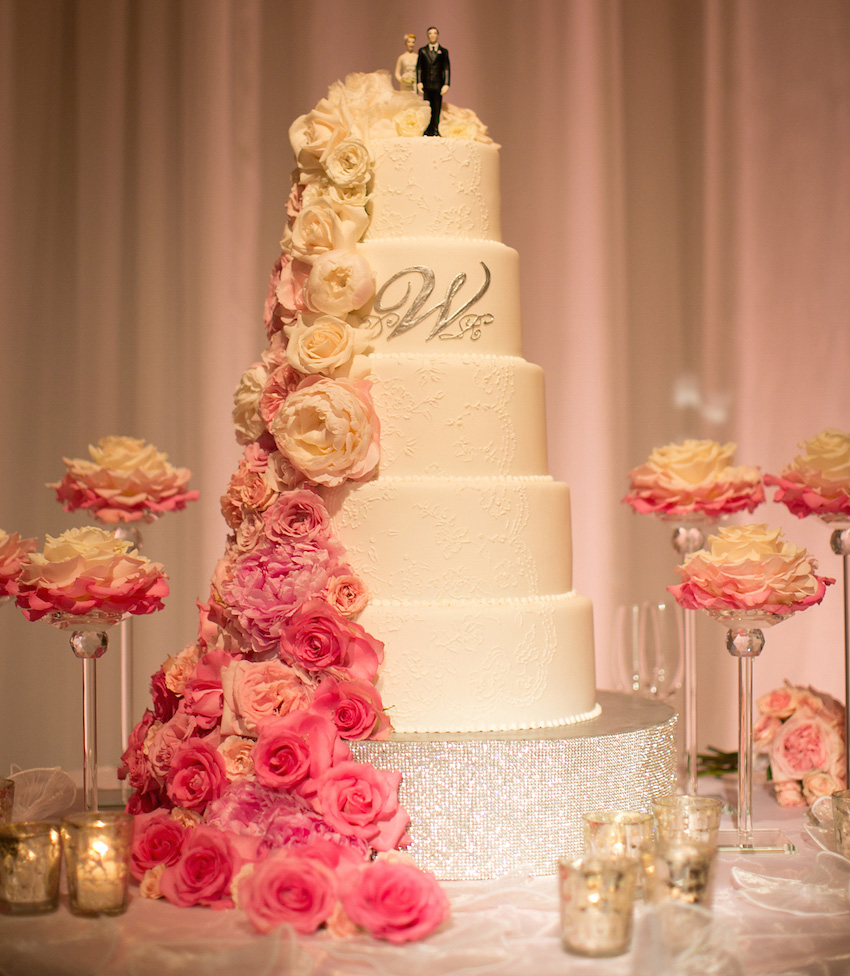 White Wedding Cake With Cascading Ombre Flowers In Pink And