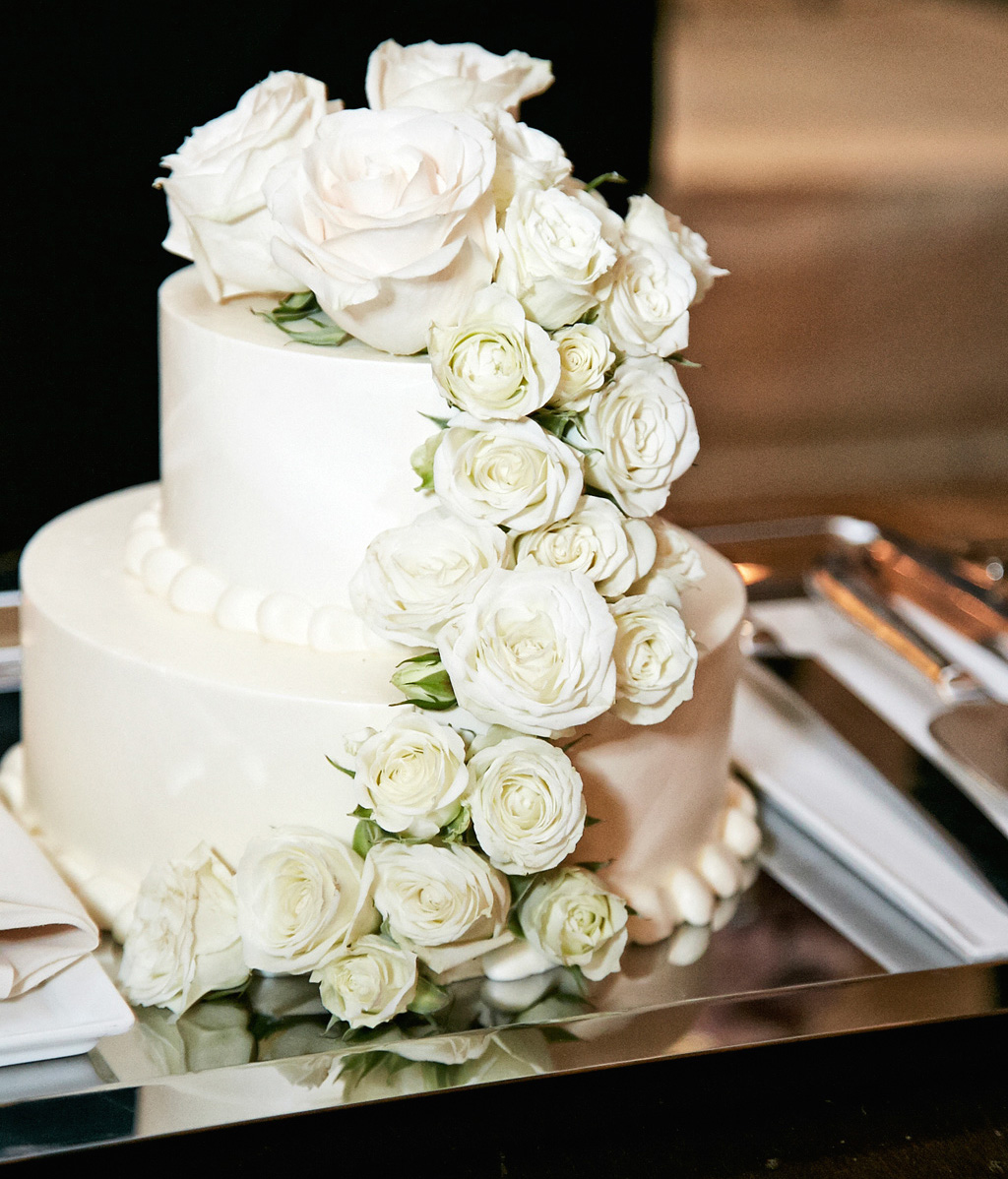 Small white wedding cake with fresh white rose flowers