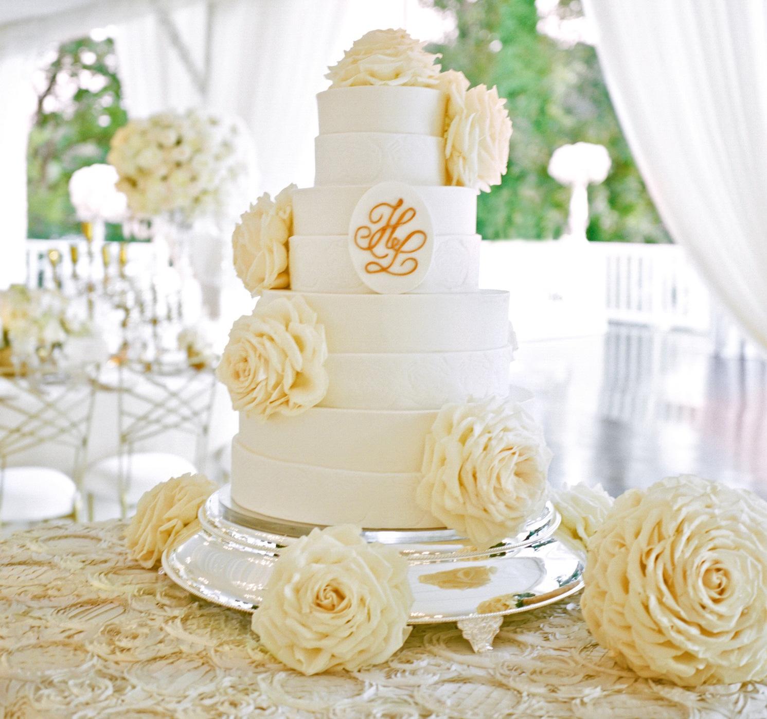 White wedding cake with monogram and glamelia flowers