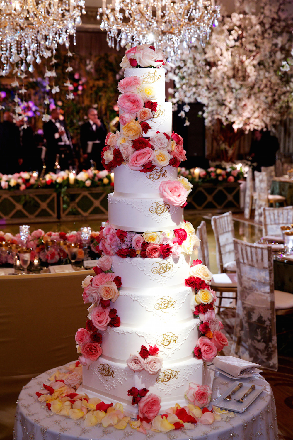 Huge and tall wedding cake with fresh red and pink flowers