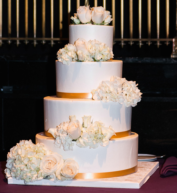 White wedding cake with gold ribbon and fresh white flowers