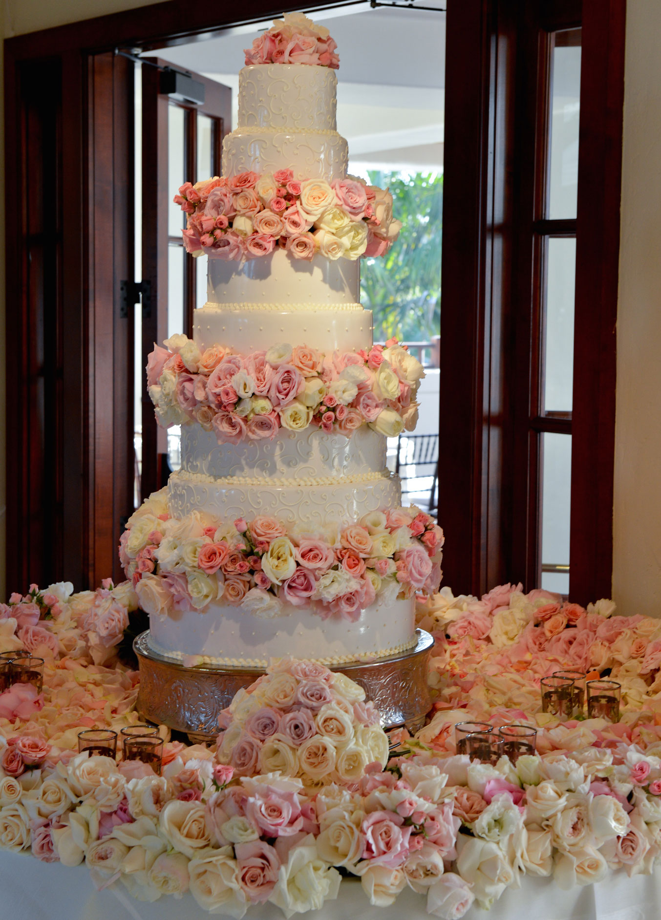 Tall white wedding cake with fresh pink and white flowers