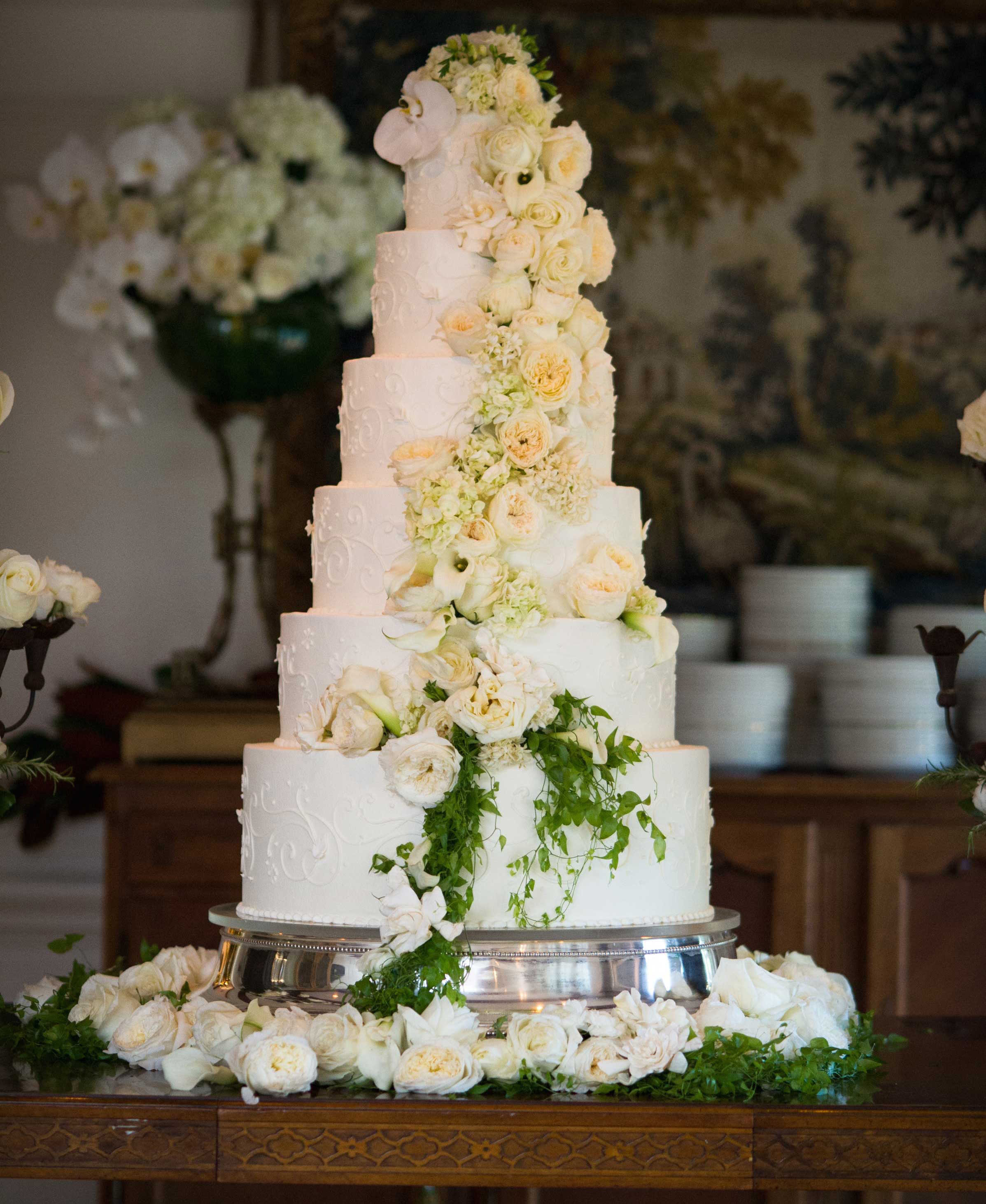 Tall white wedding cake with fresh white flowers