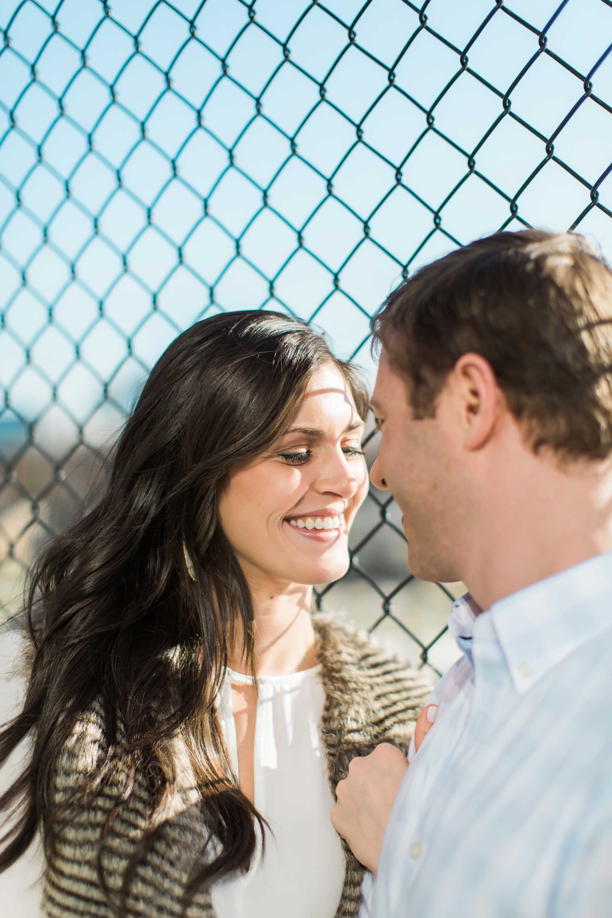 Bride smiles in front of chain link fence at Vue Photography engagement session