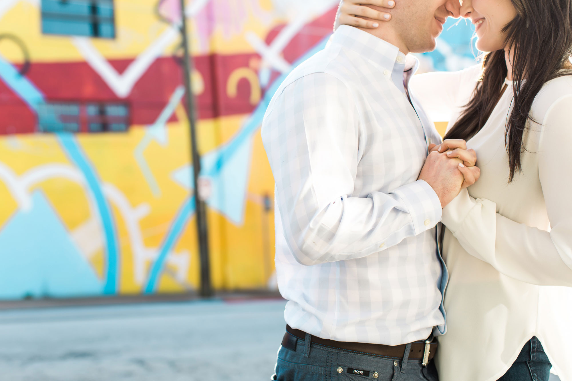 Close up of bride and groom holding hands graffiti wall Vue Photography engagement session