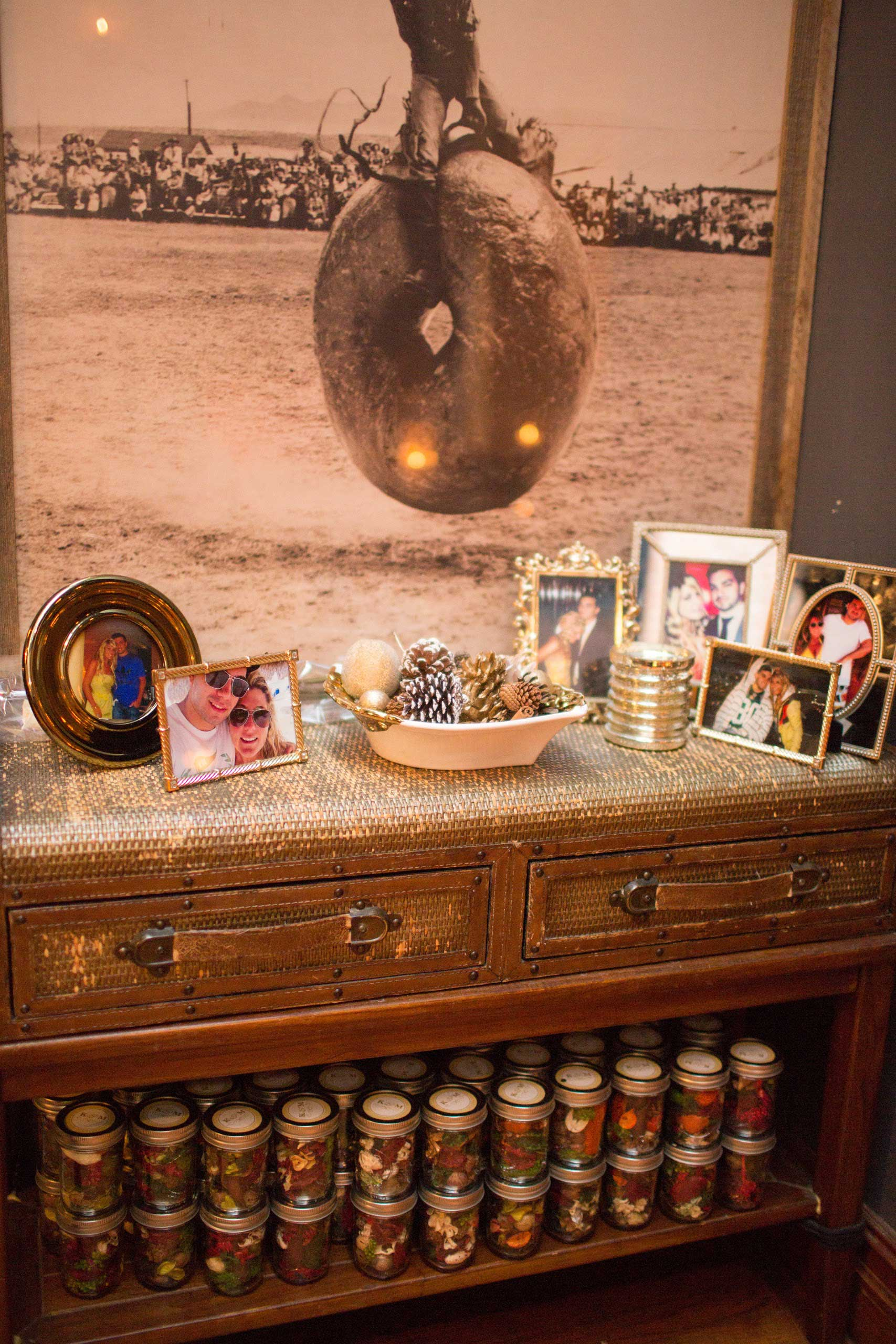 Rustic venue for engagement party with frames of couple and pot pourri favors