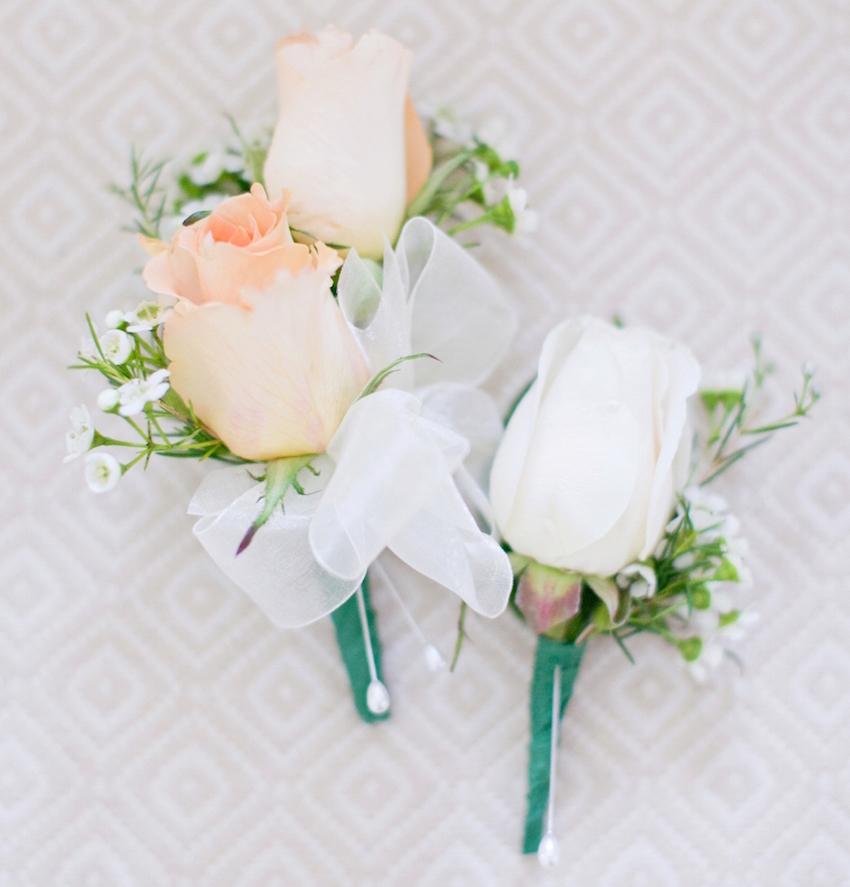 White and pastel orange wedding boutonniere for groom groomsmen