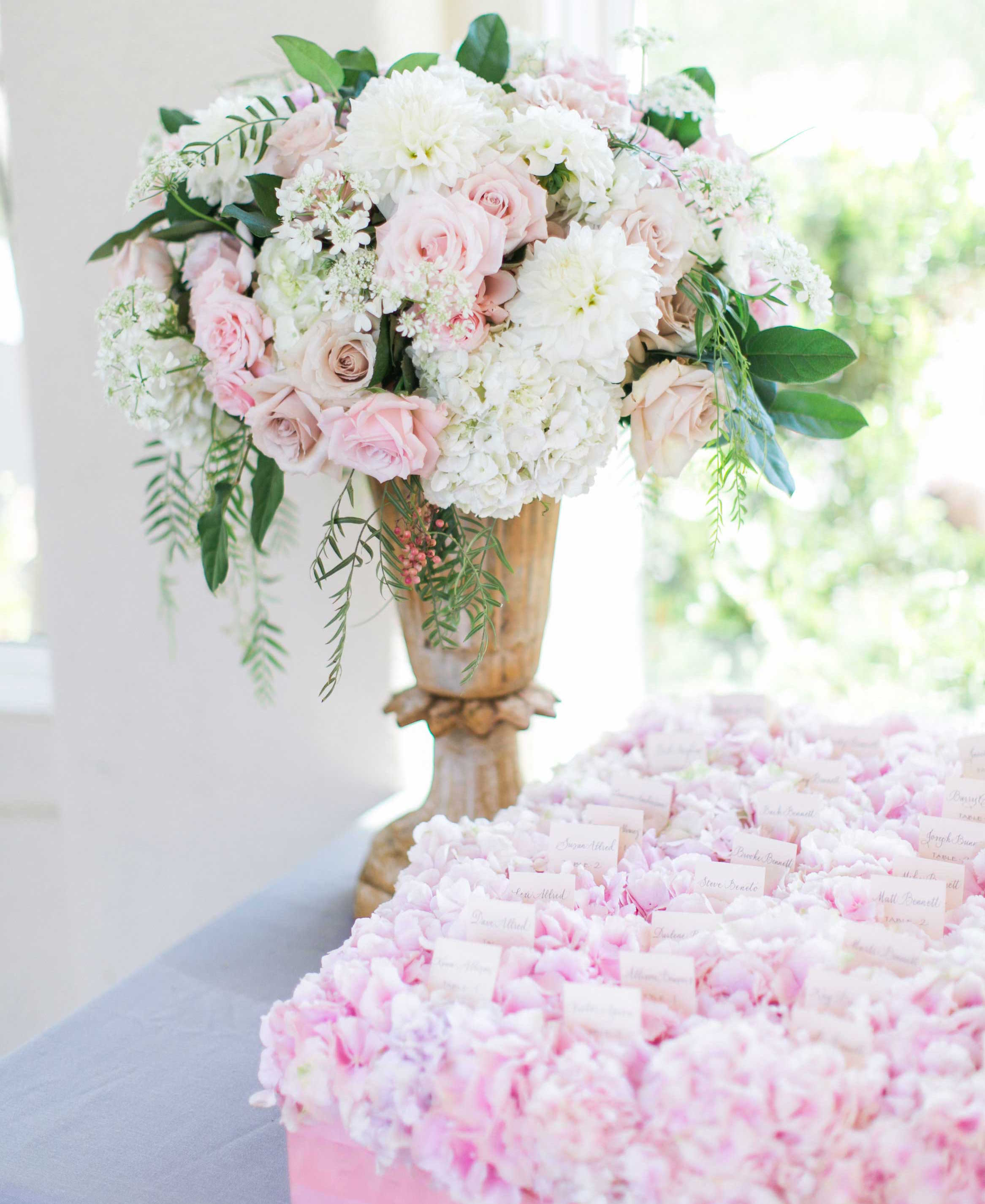 Wedding escort cards on top of light pastel pink flowers