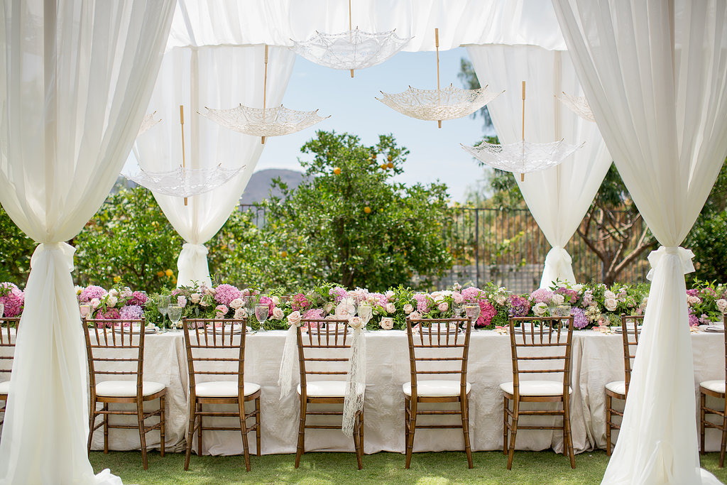 Wedding reception table outdoors with white parasols and pastel flowers