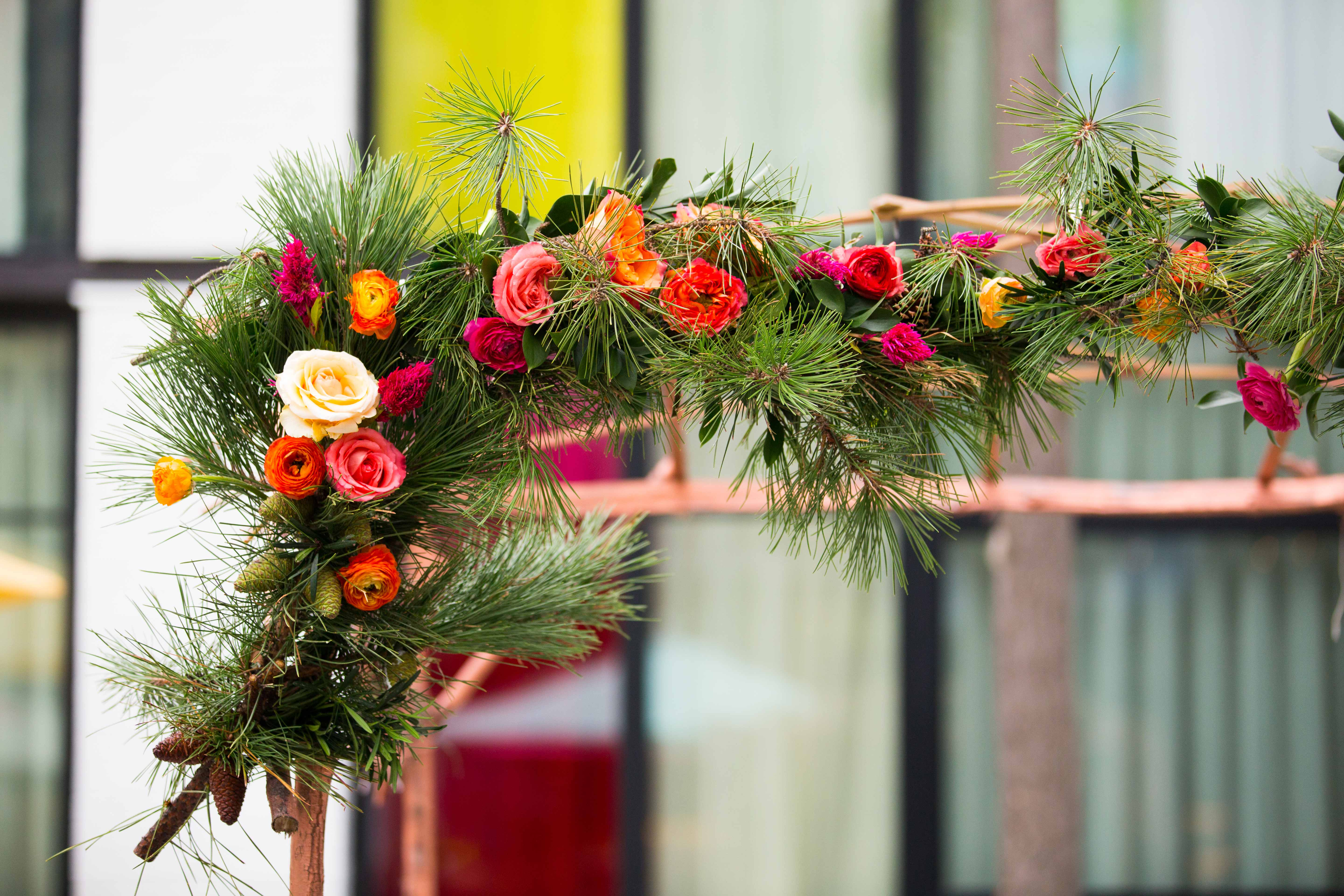 Ceremony arch chuppah with green pine needles and vibrant colorful flowers