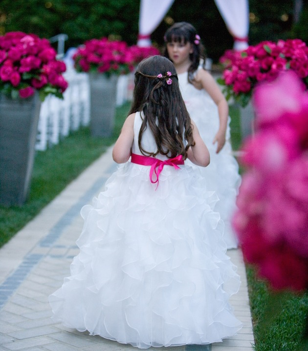 Flower girls in white ruffle skirt dresses with hot pink ribbon