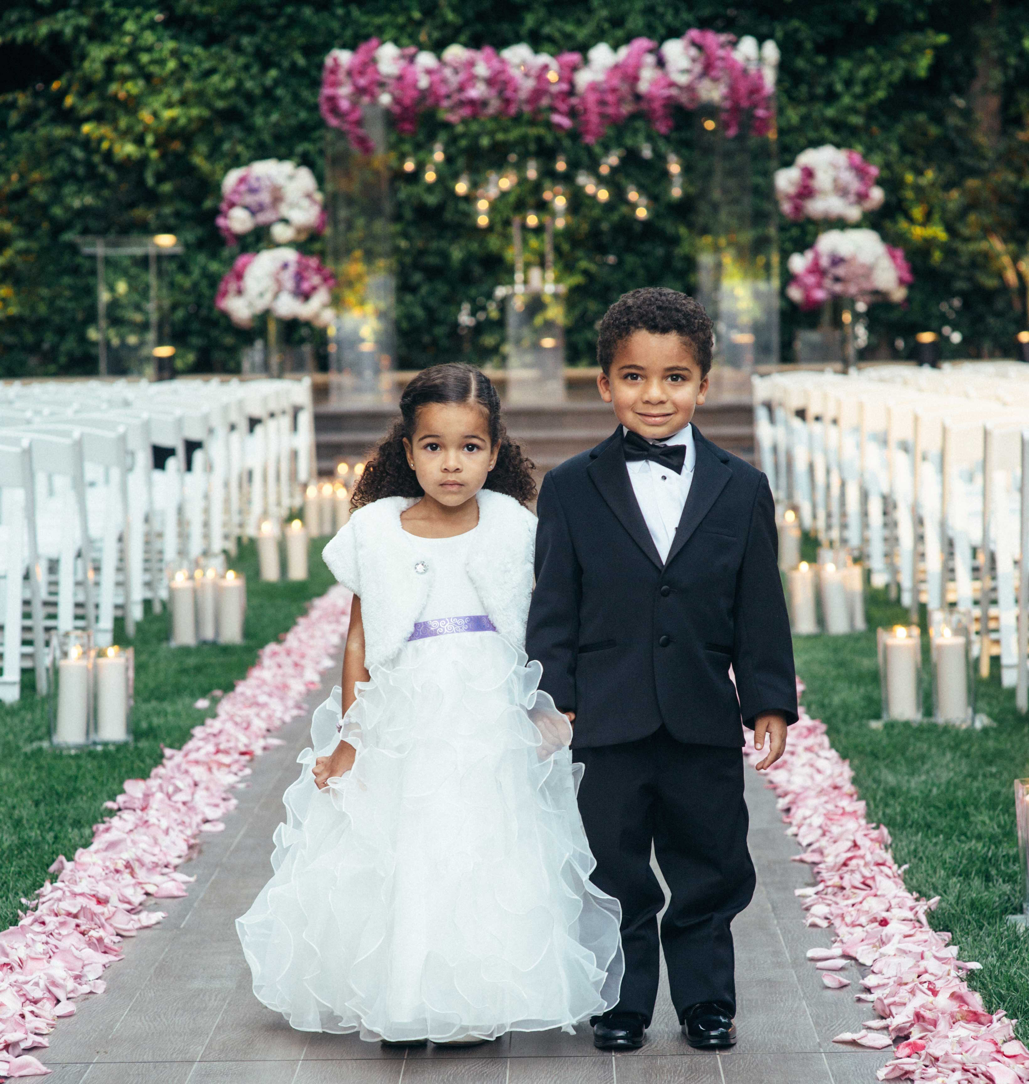 Flower girl in ruffle dress with purple ribbon and ring bearer at outdoor wedding