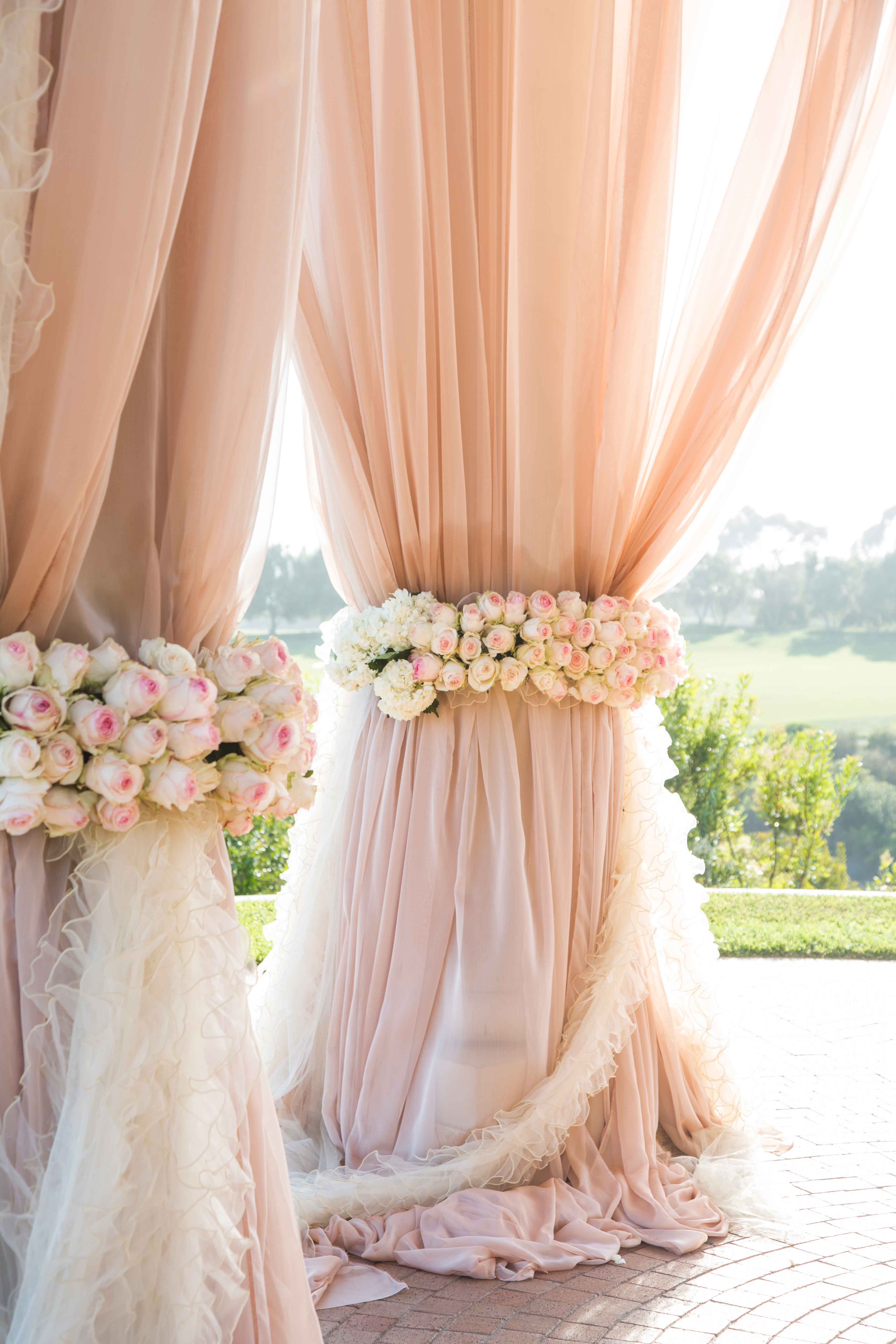 Pink drapery at outdoor wedding ceremony chuppah with ruffle ribbon