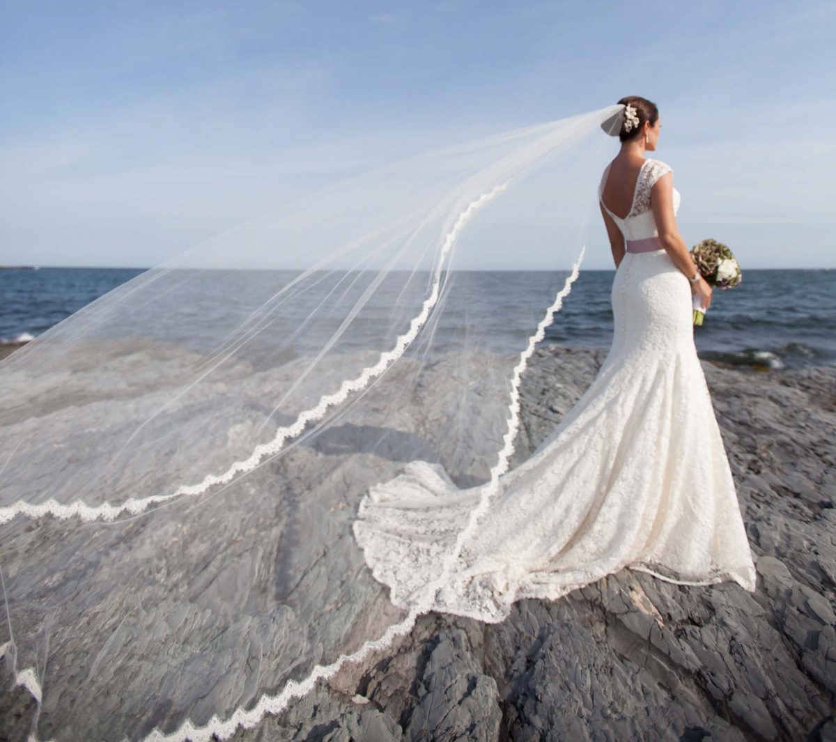 lace trim cathedral veil blows in the sea breeze